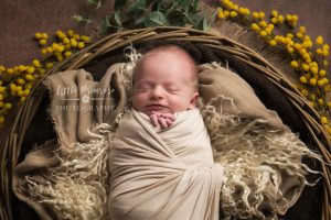 Newborn photography Alsager - Smiling baby in basket prop with blossoms