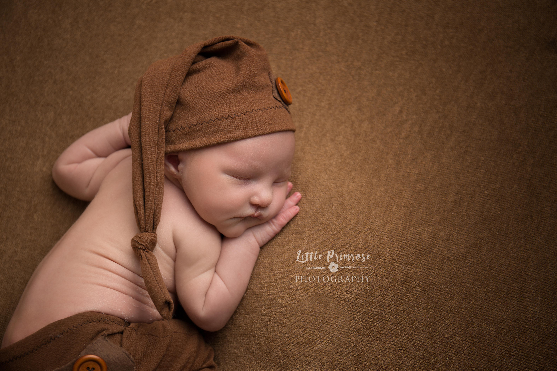Newborn in tushi up in mustard brown