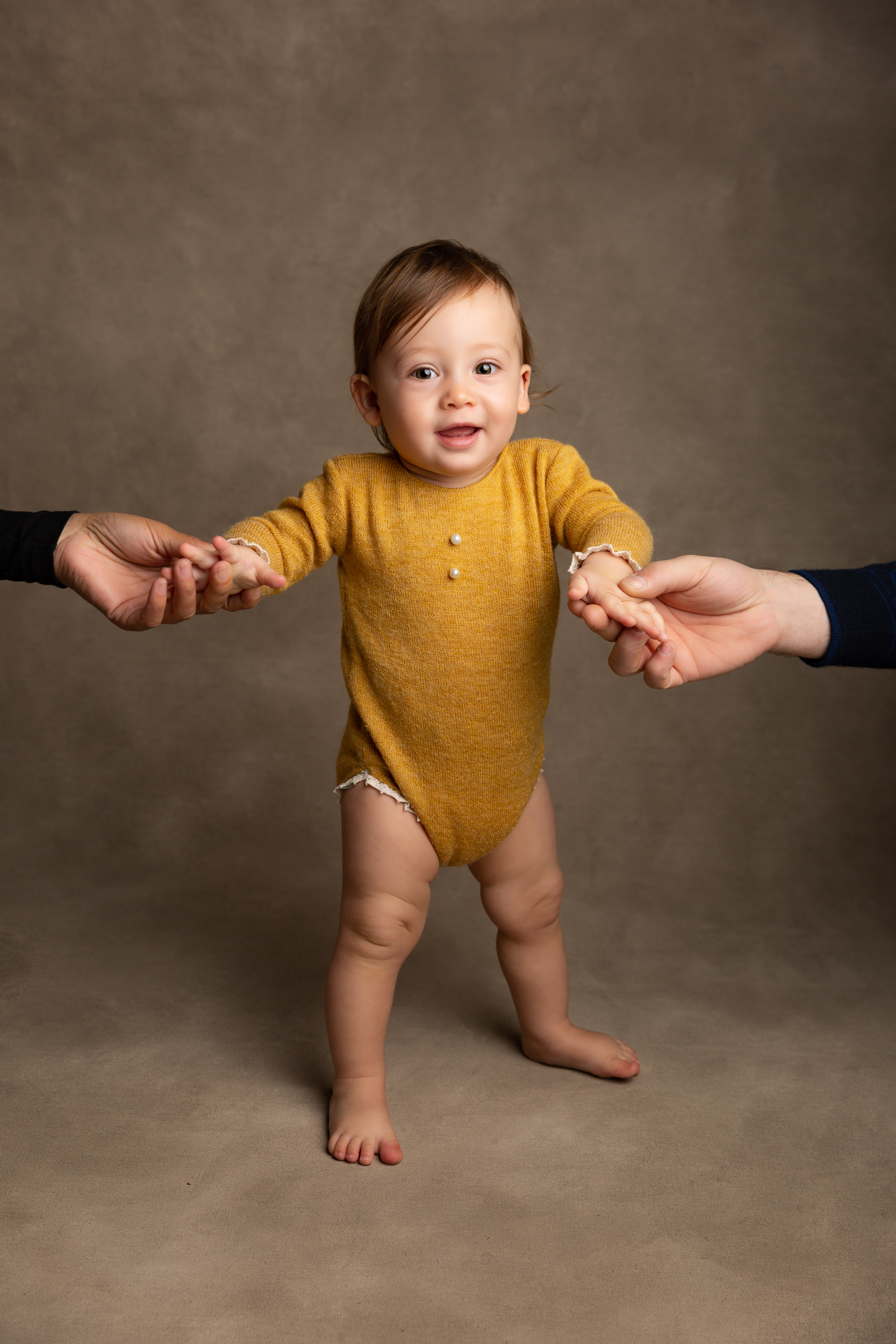 Little girl in a mustard romper holding her parents' hands
