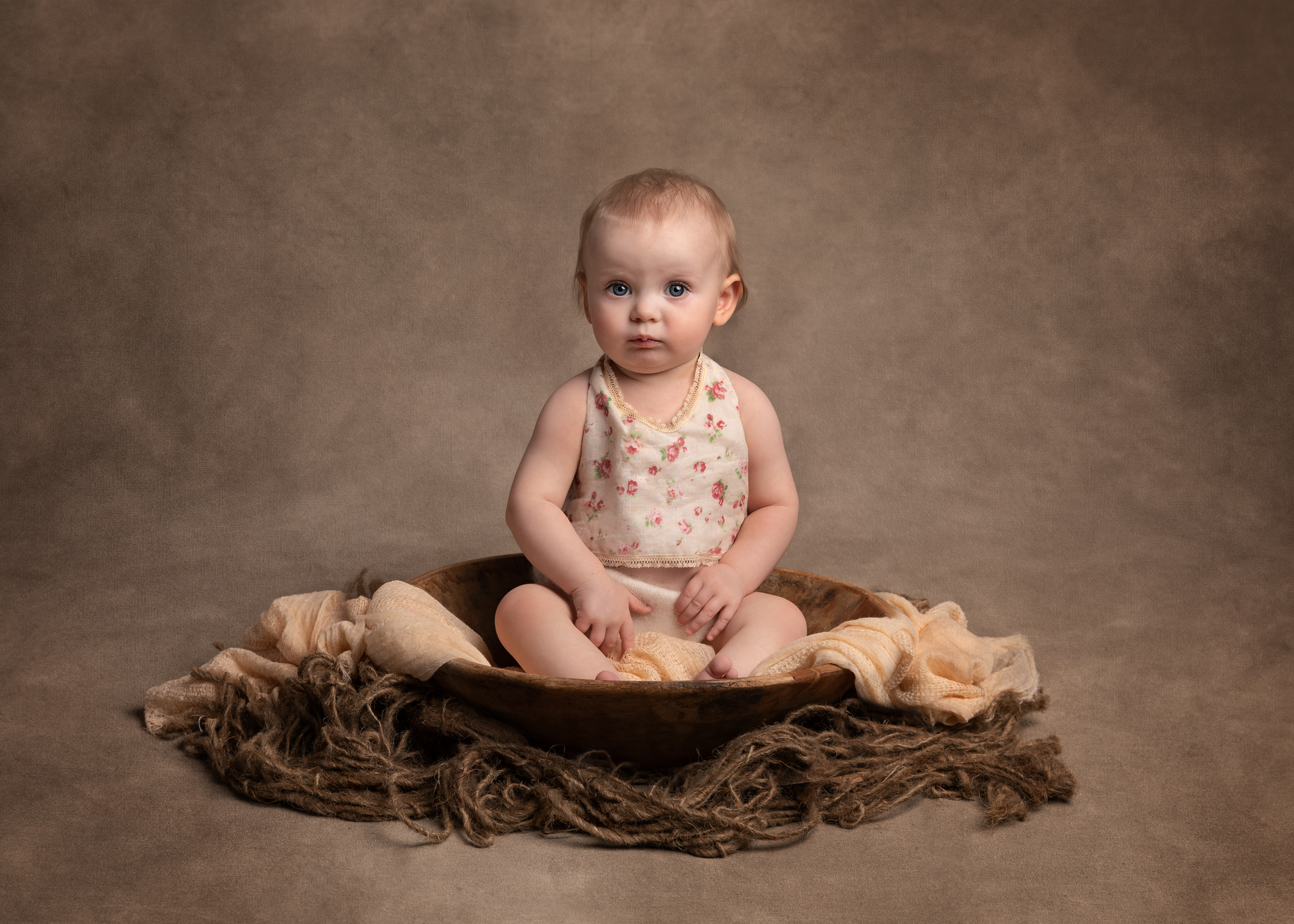 Neutral themed photo of a 1 year old girl during her birthday photo shoot in Cheshire
