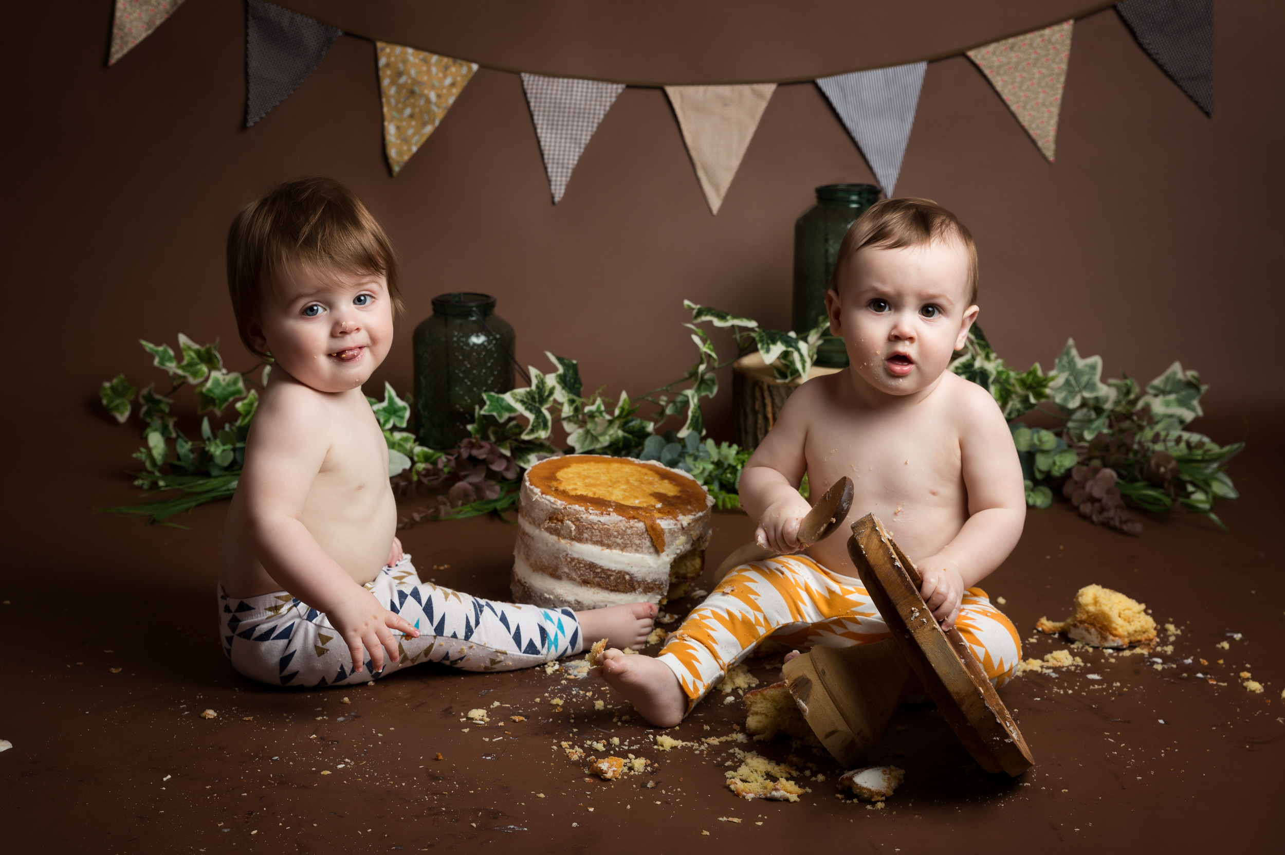 Twin boys enjoying their cake smash photo shoot in Cheshire