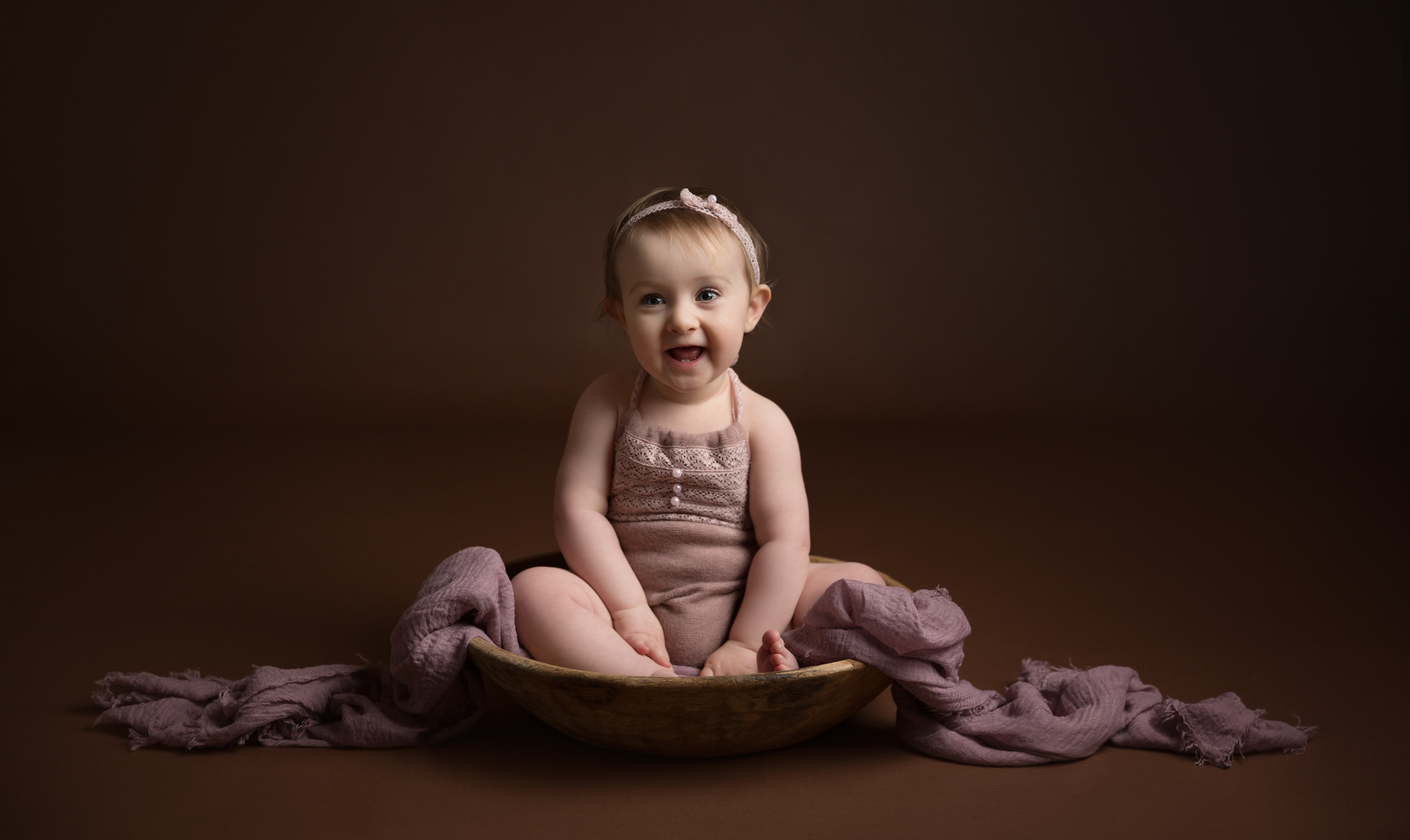 Little girl in a pink romper on a brown backdrop during her photo shoot in Cheshire