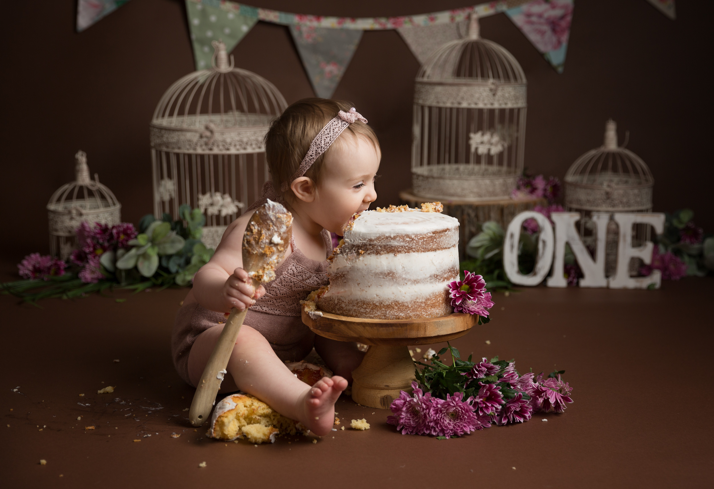 1 year old baby girl biting into her cake during her cake smash photo shoot in Cheshire