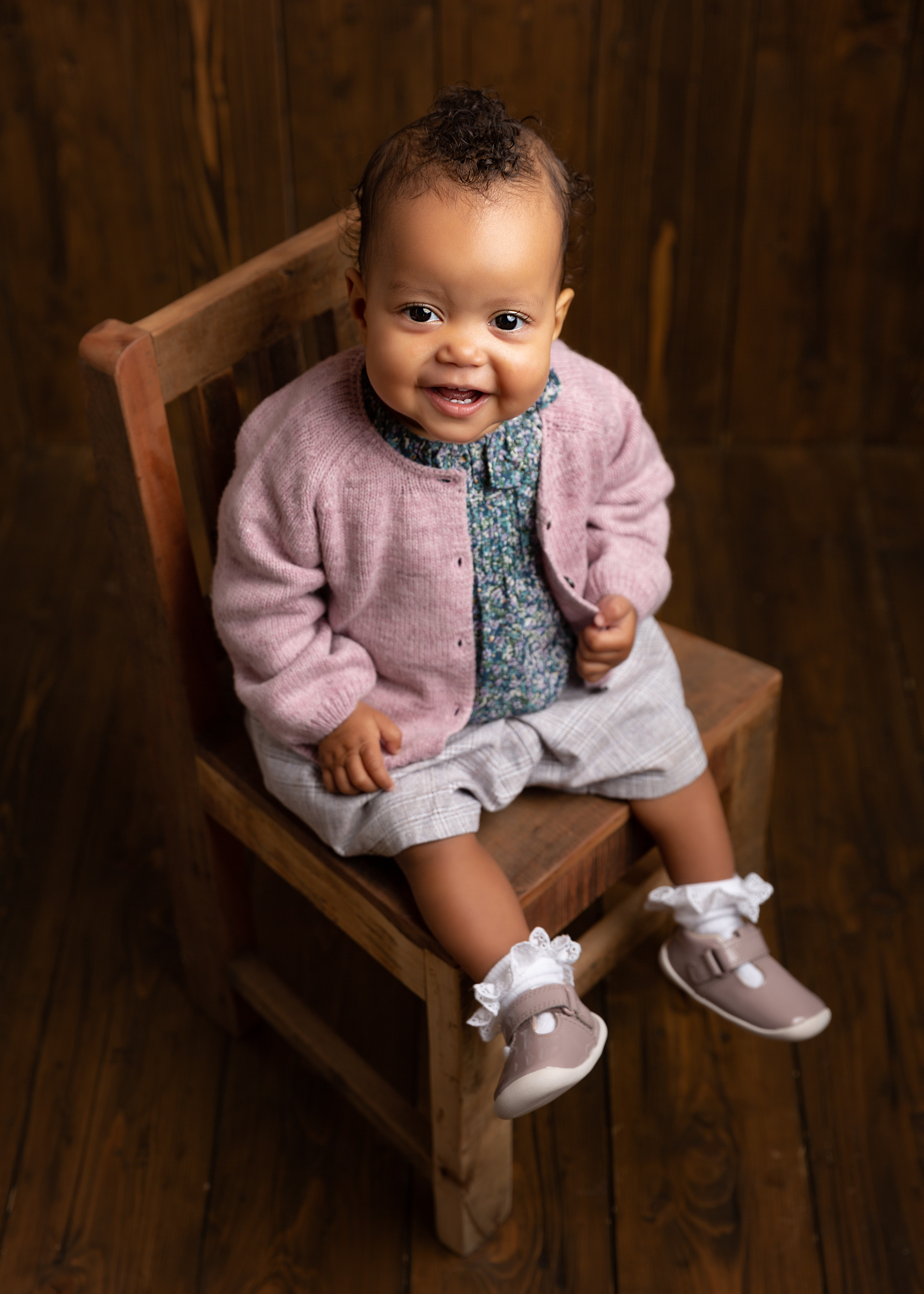 Little girl sitting on a vintage chair at her photoshoot in Cheshire