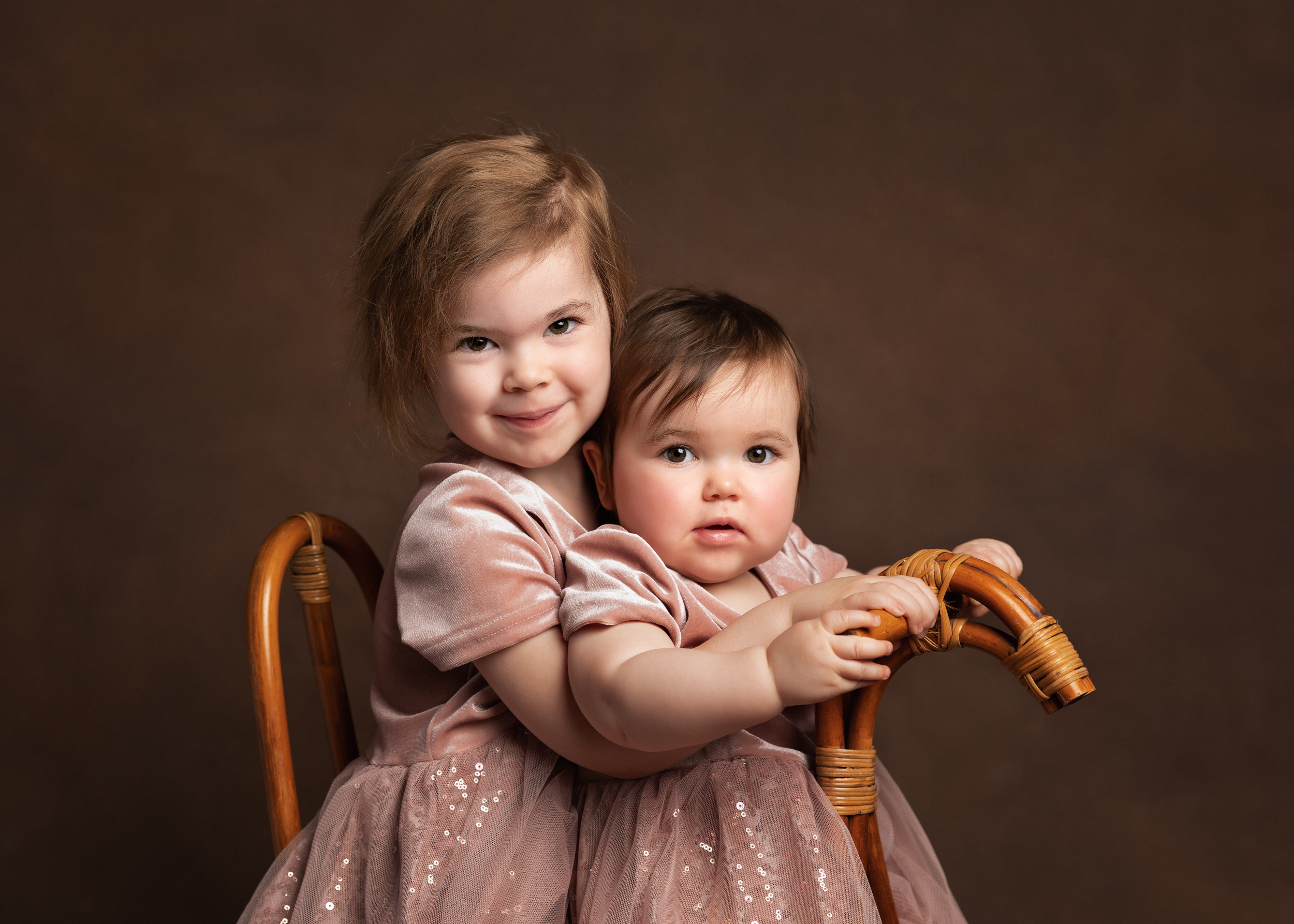 Sisters on a rocking horse for a family portrait in Sandbach, Cheshire