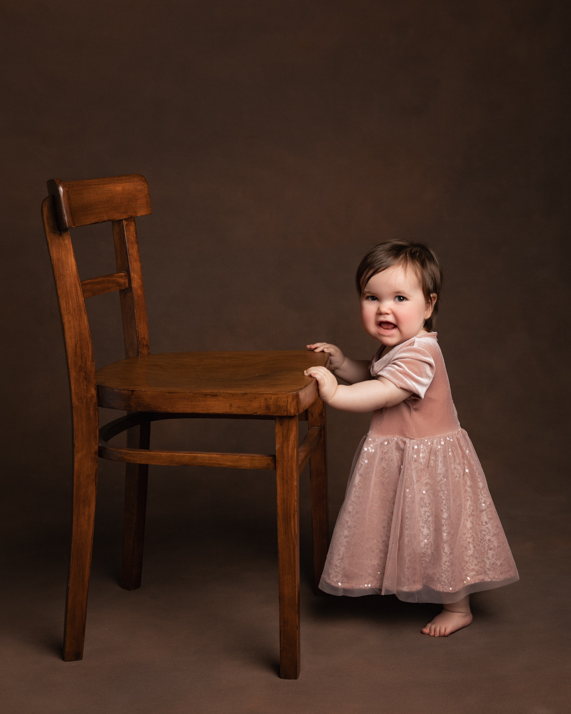Little girl holding onto a chair during her birthday shoot in Sandbach, Cheshire