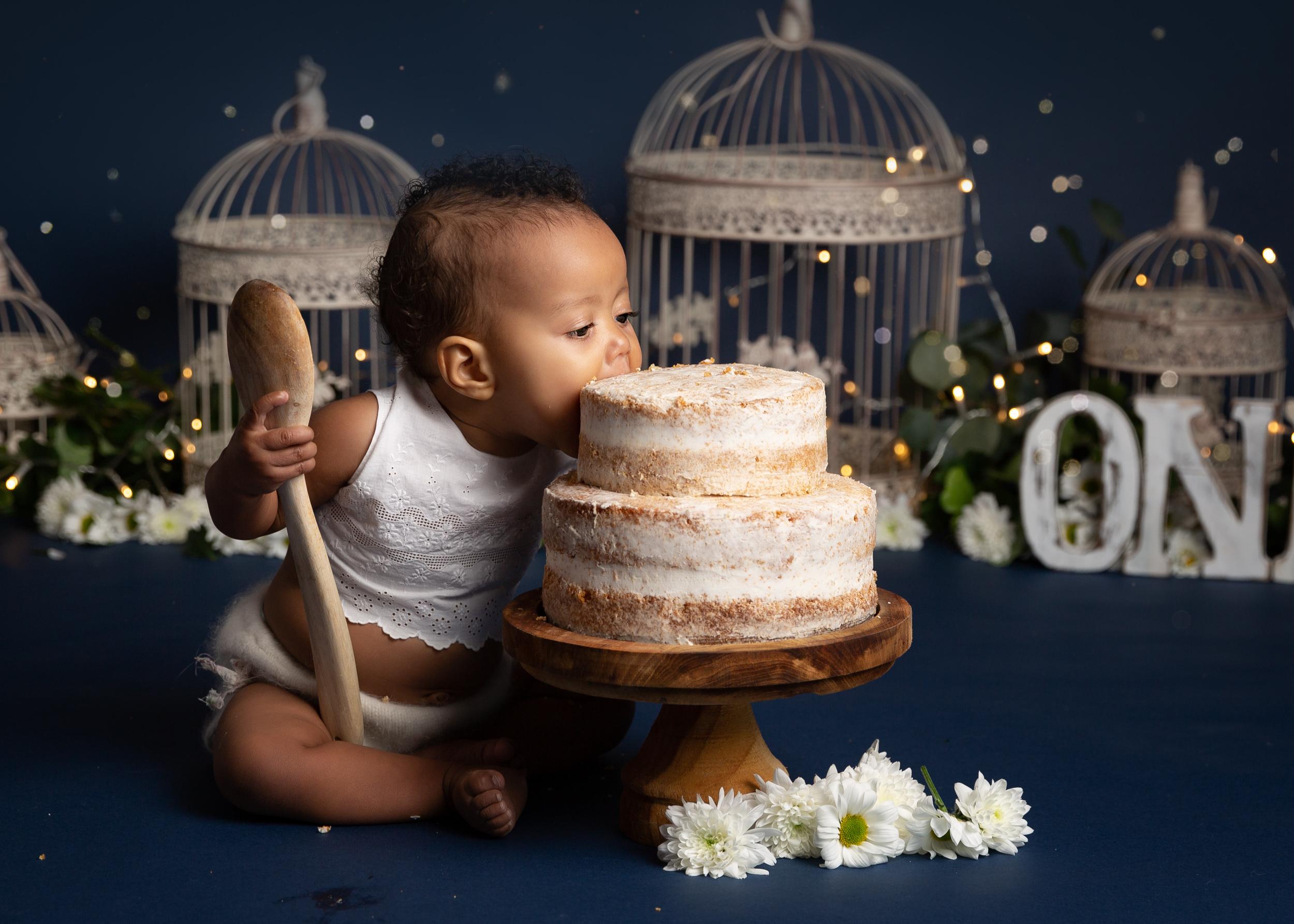 Little girl munching her cake during her photo shoot in Cheshire