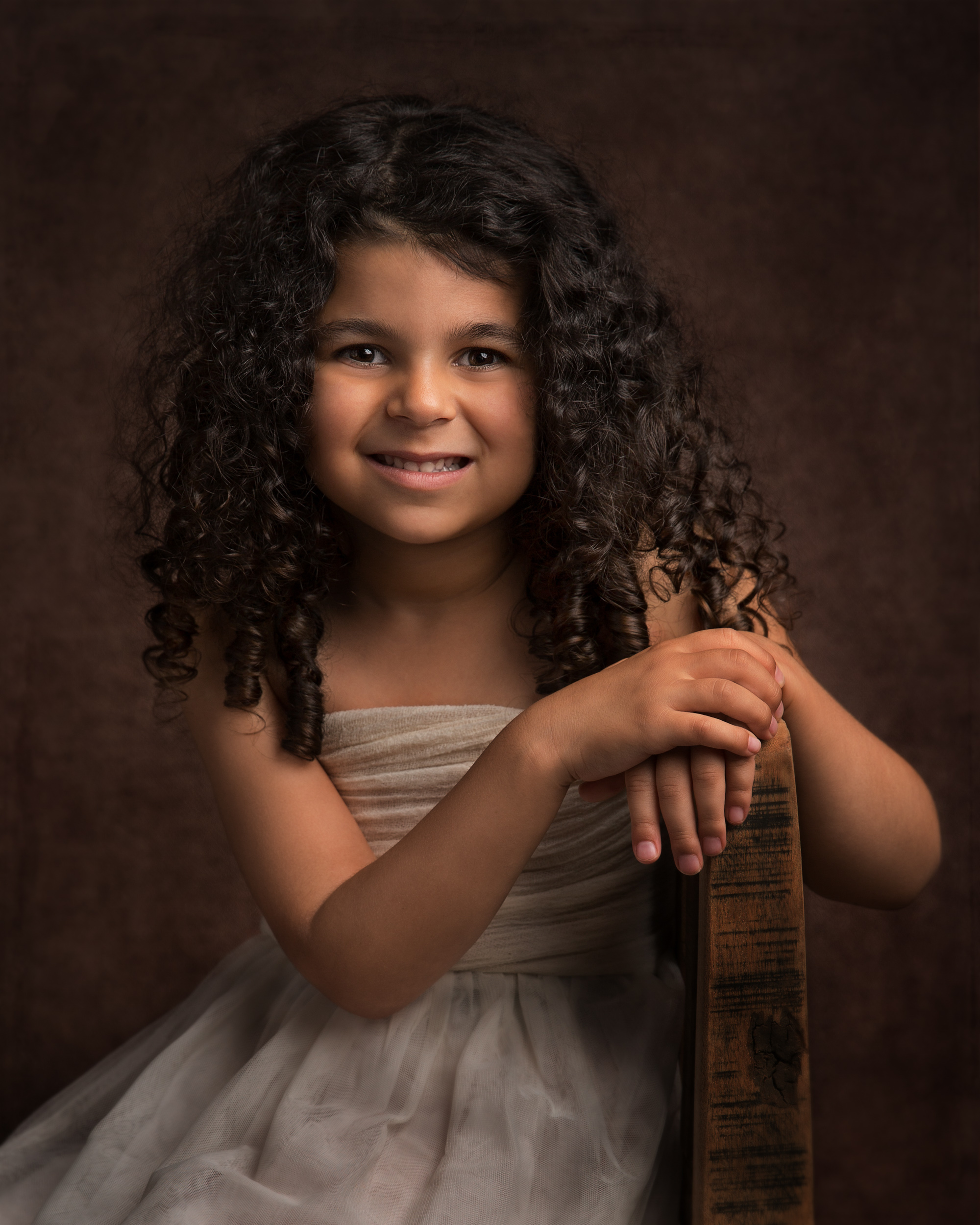 Beautiful little girl with curly hair taken during a family portrait session in Cheshire