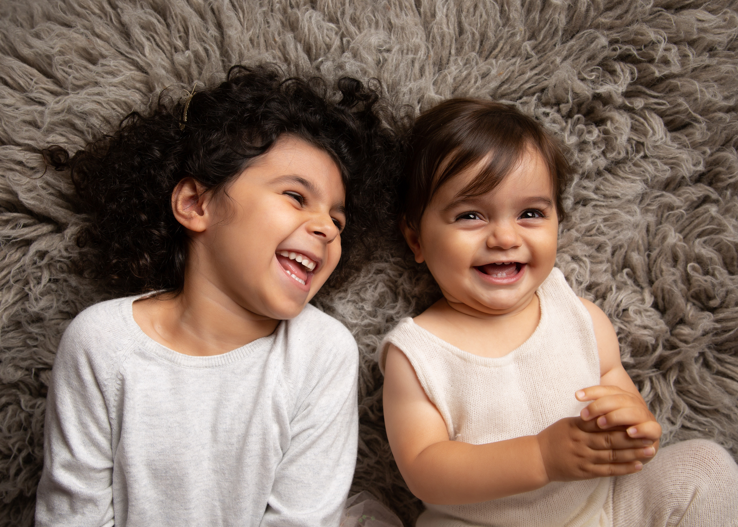 Siblings laughing together at their family portrait session in Cheshire