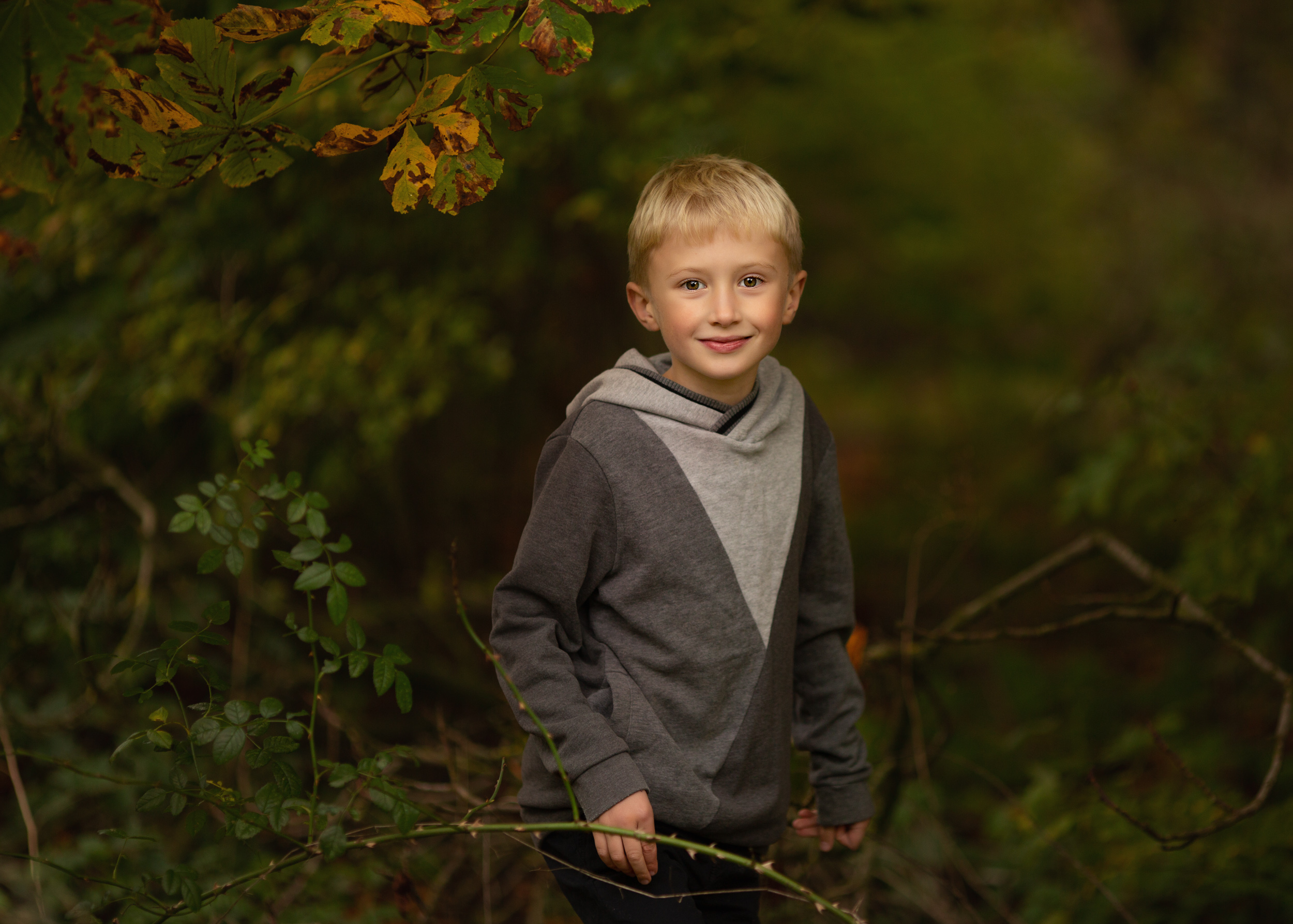 A little boy sneaking through trees at an outdoor family portrait with autumn tones in Nantwich, Cheshire