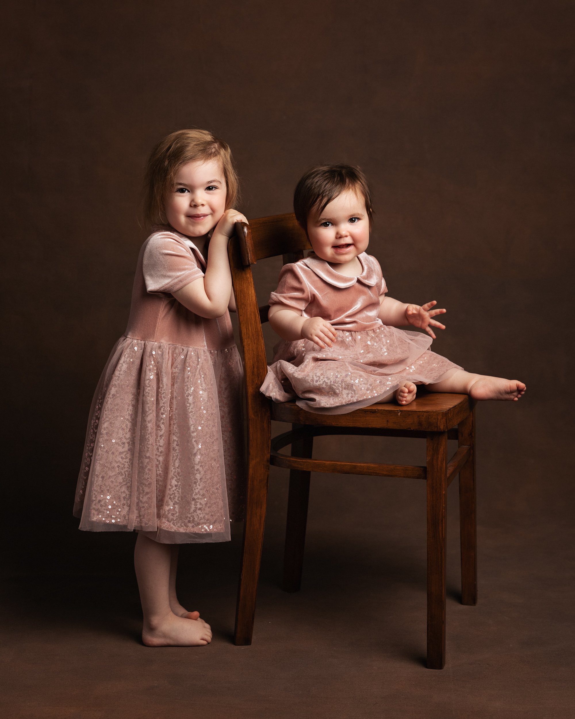 Sisters in the same pink dress posing together on a chair for their Family Portrait photo shoot in Cheshire