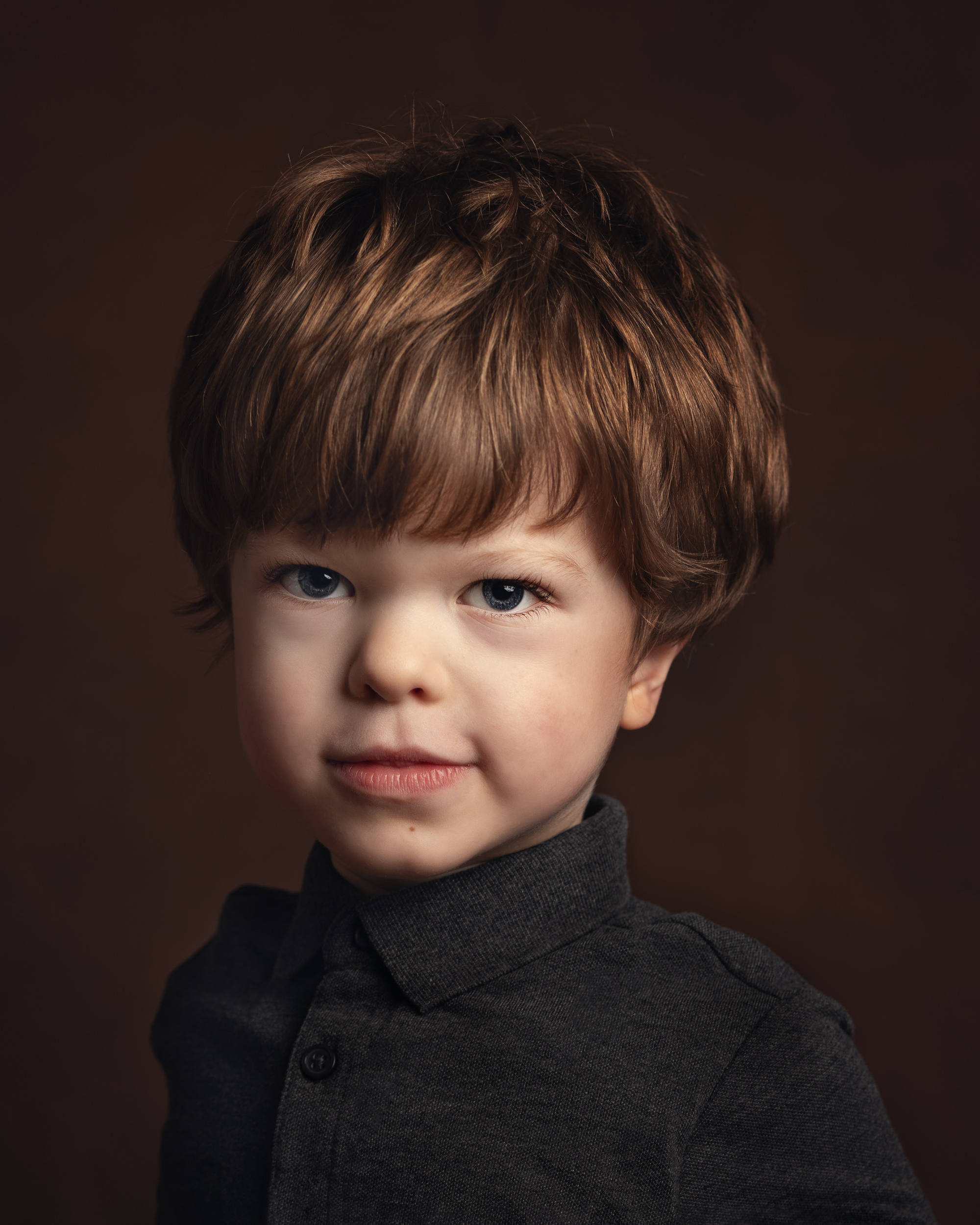 Rufus, who has achondroplasia, with a serious face on during his portrait session in Cheshire