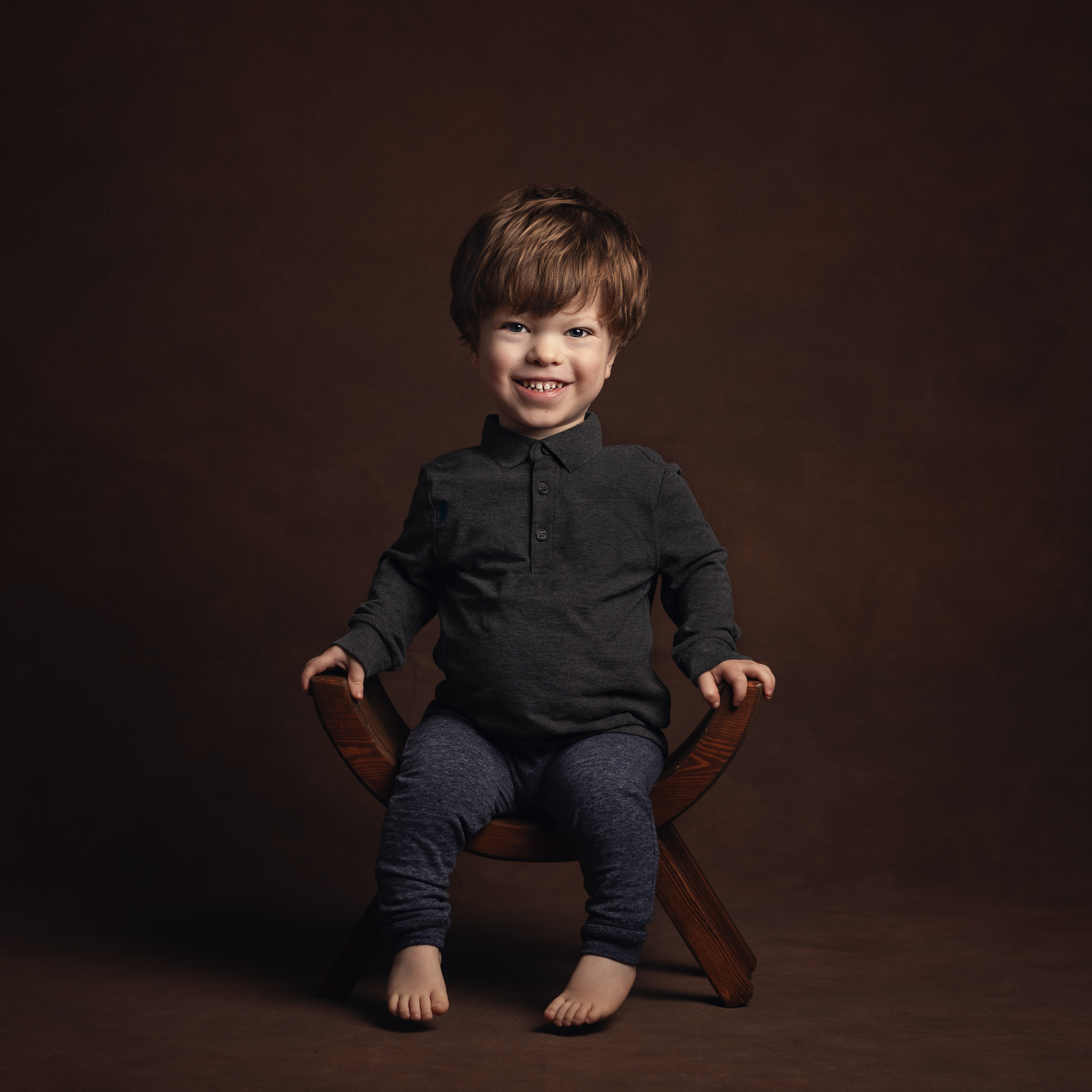 Rufus, who has achondroplasia, smiling during his portrait session in Cheshire