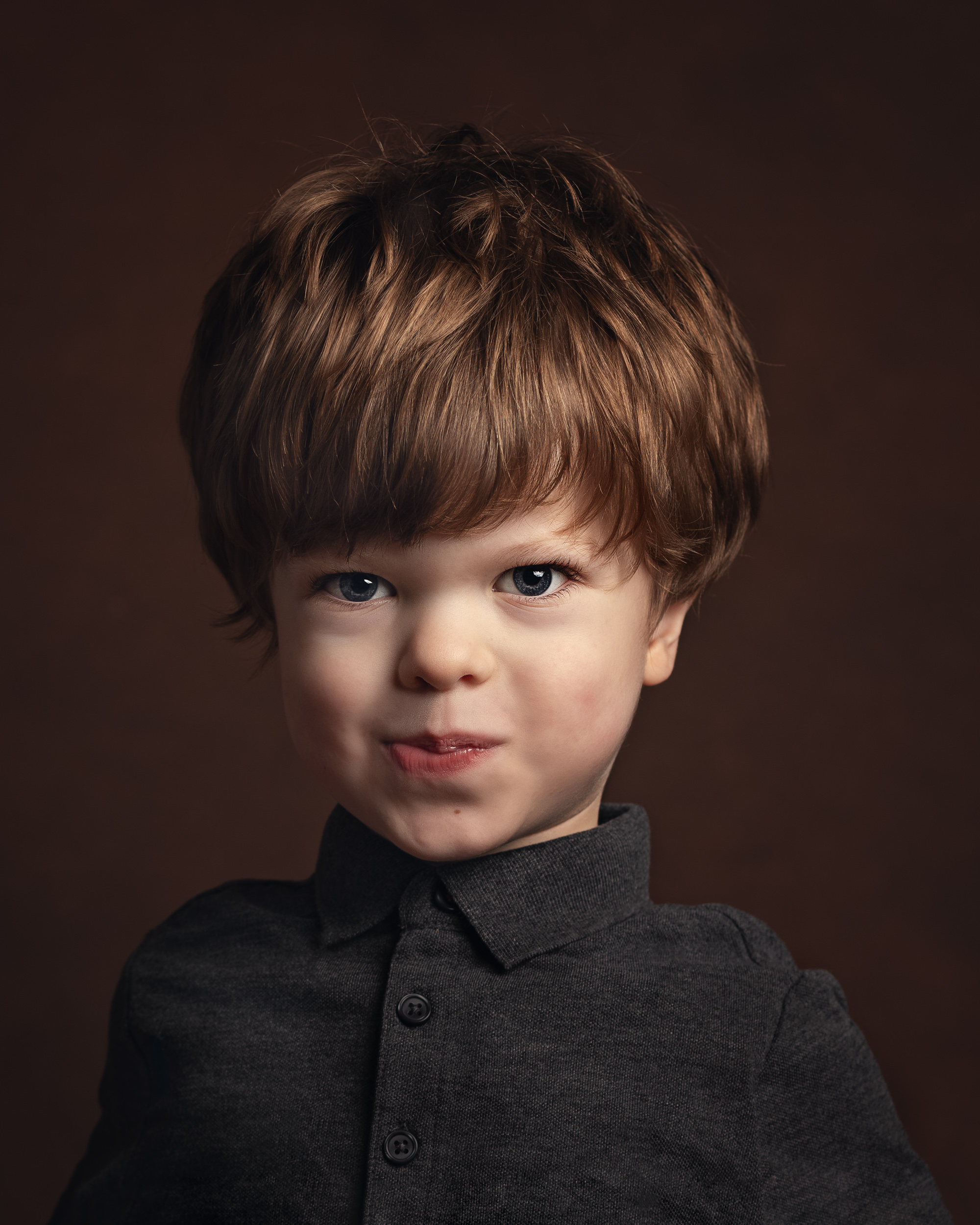 Rufus, who has achondroplasia, with a cheeky face on during his portrait session in Cheshire