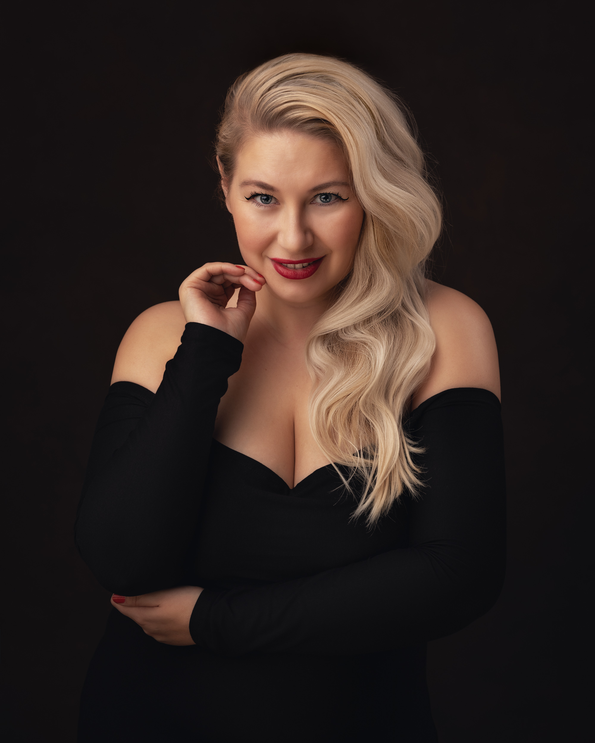 A glamorous portrait of a blonde singer in a black dress at her head shot session in Cheshire