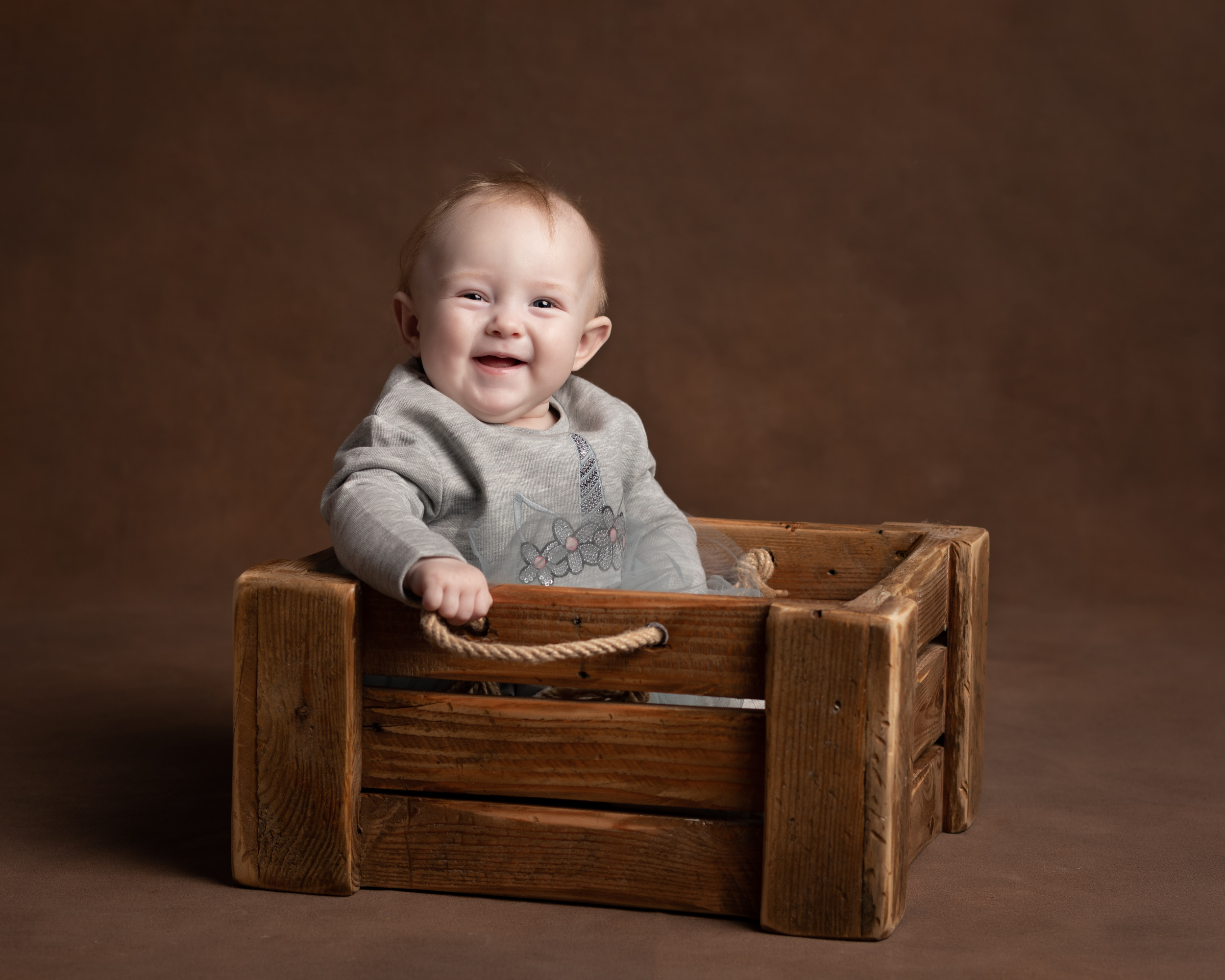 6 month old baby sitting in a crate during her Family Portrait photoshoot in Cheshire