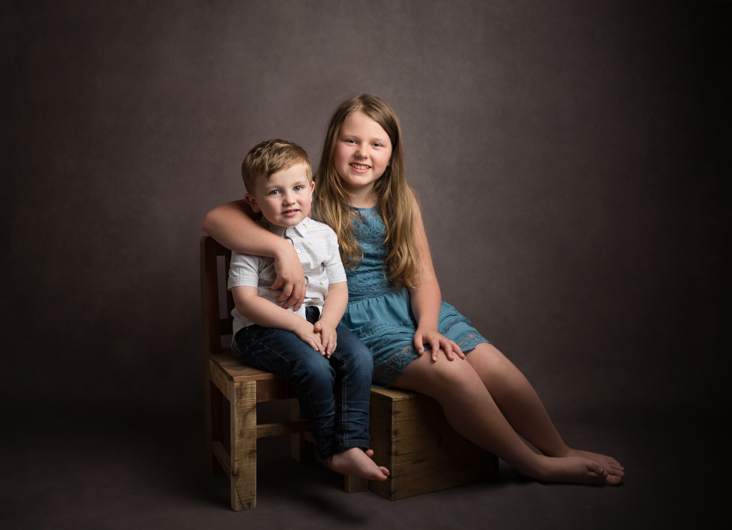 Siblings sitting together at their family portrait session in Cheshire