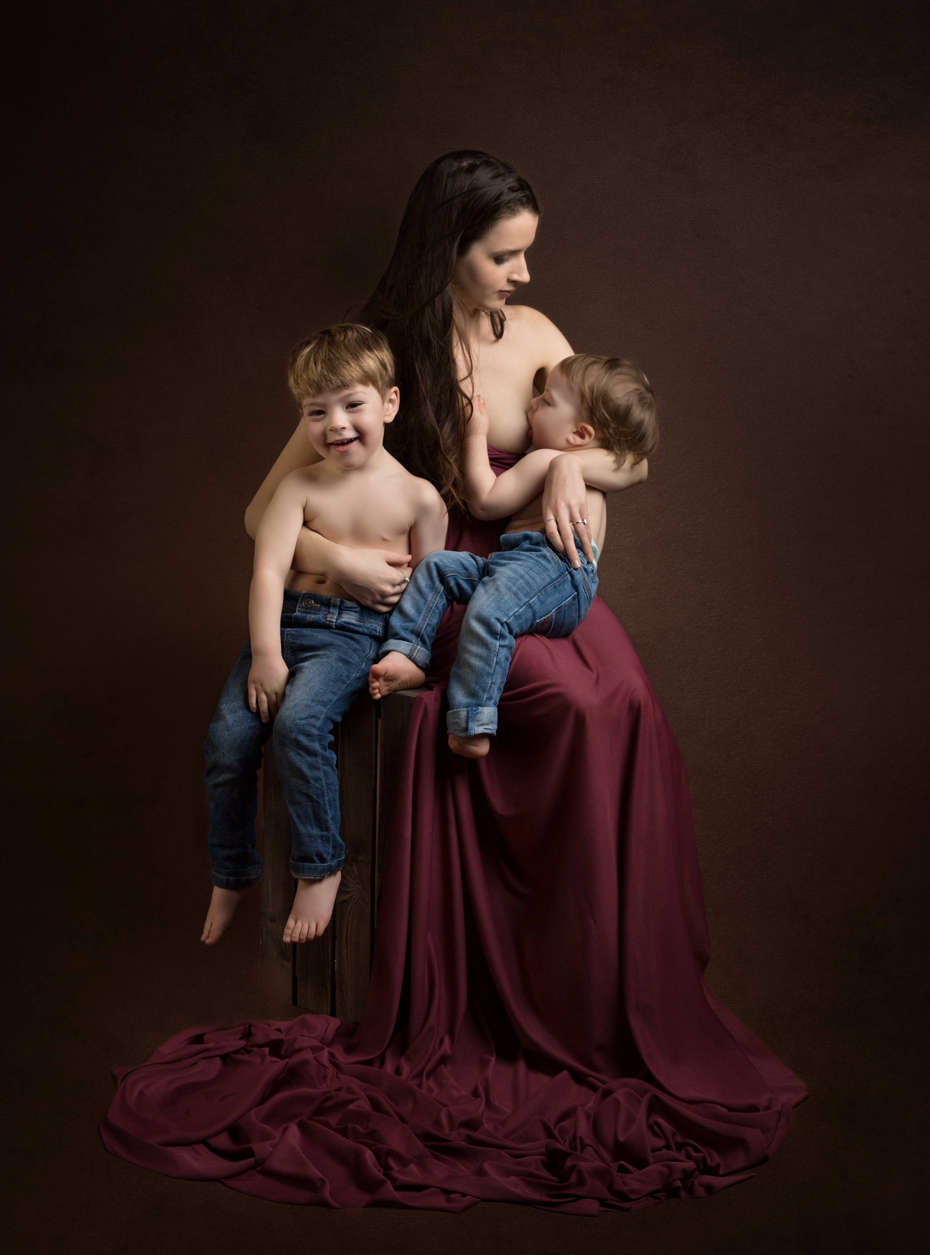 Subtle breastfeeding image with stunning gown and two boys in jeans in Cheshire