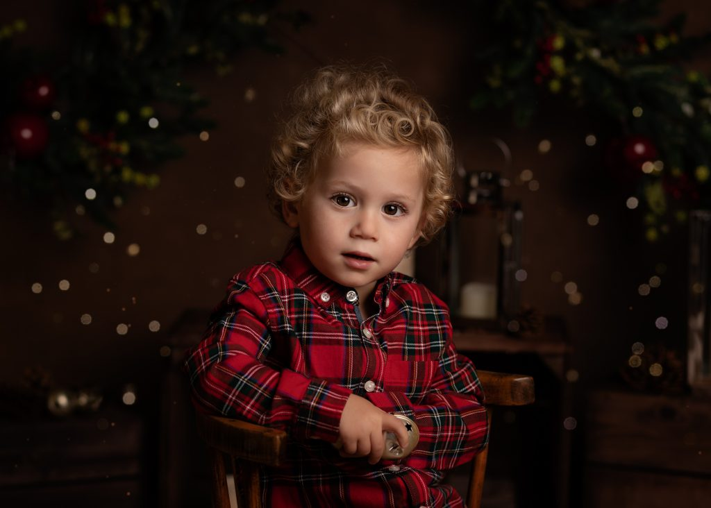 A little boy in a red shirt posing for his Christmas Mini Session photo shoot in Cheshire