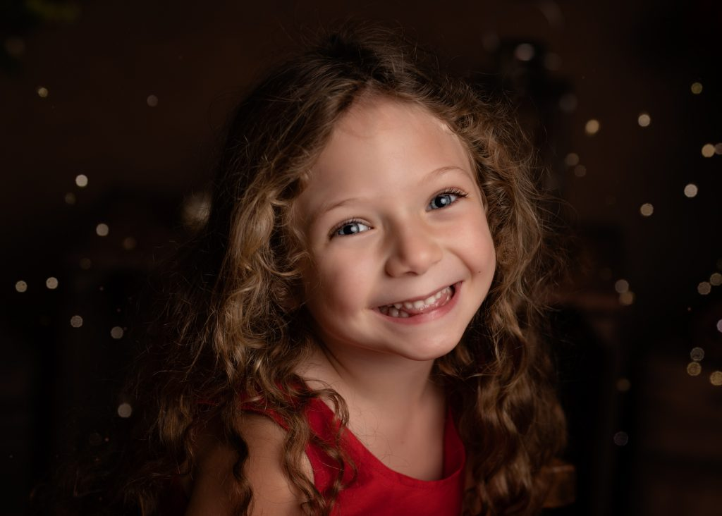 Close up of a little girl in her red dress posing for her Christmas Mini Session photo shoot in Cheshire