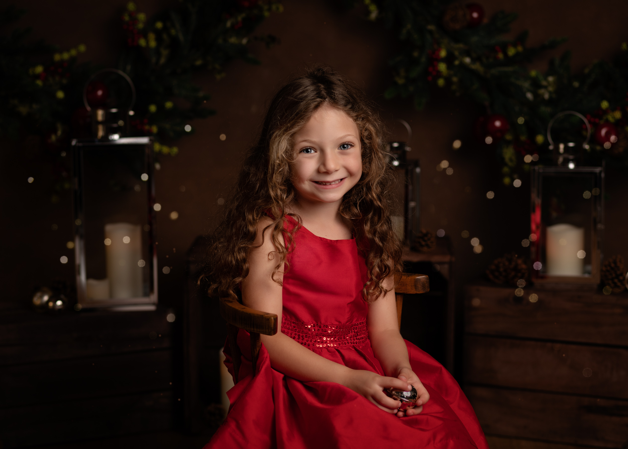 Little girl in a red dress posing for her Christmas Mini Session photo shoot in Cheshire