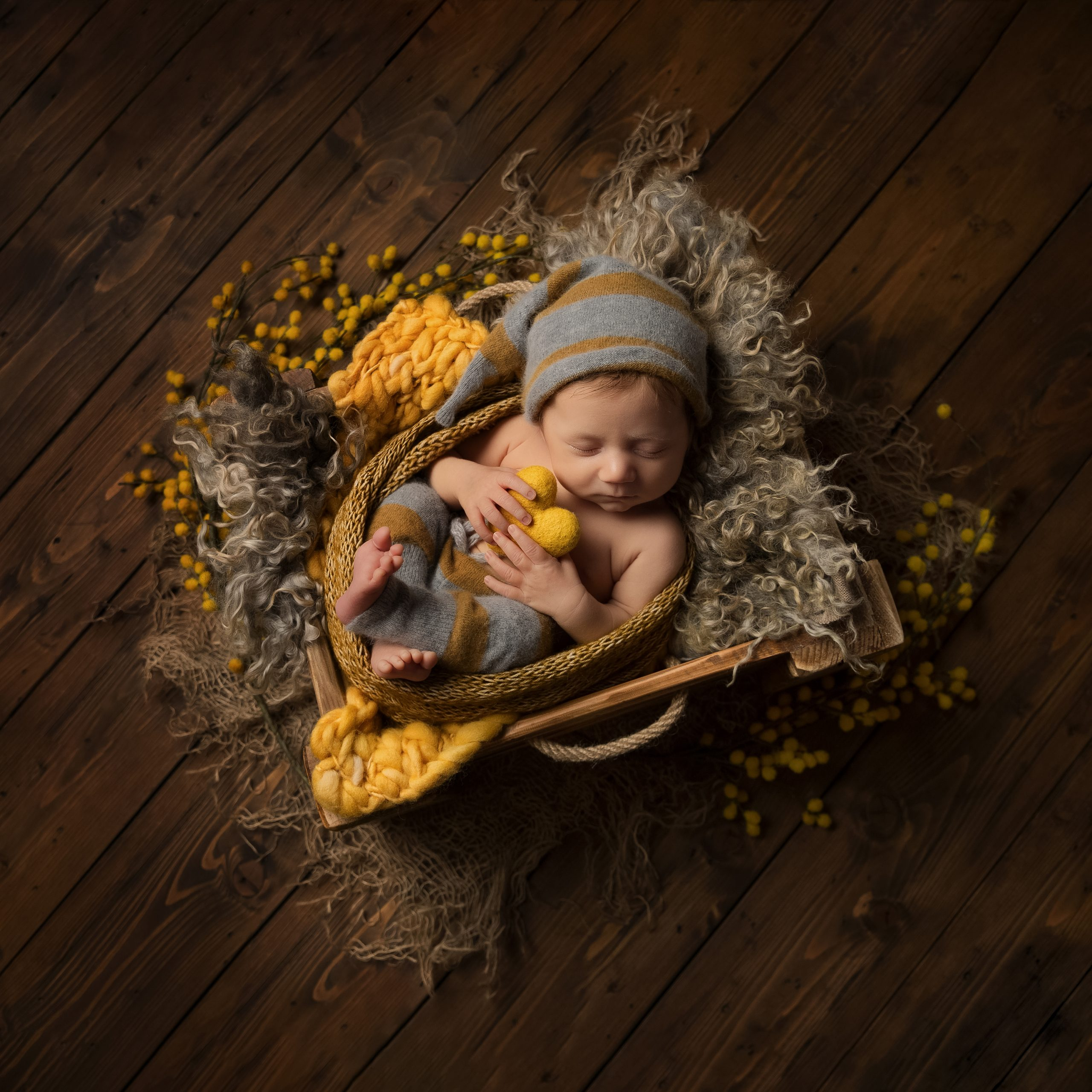 Newborn baby holding a yellow heart as part of my Master Craftsman in Newborn Photography panel by award winning photographer