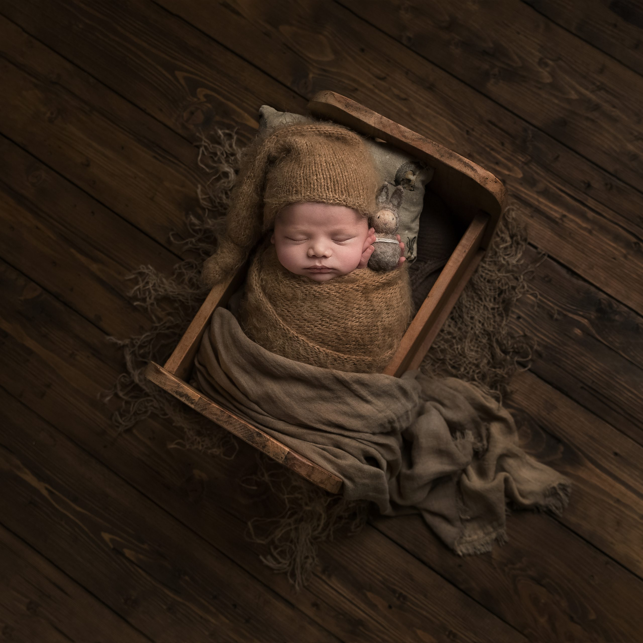 Newborn baby wrapped and in a little bed as part of my Master Craftsman in Newborn Photography panel by award winning photographer