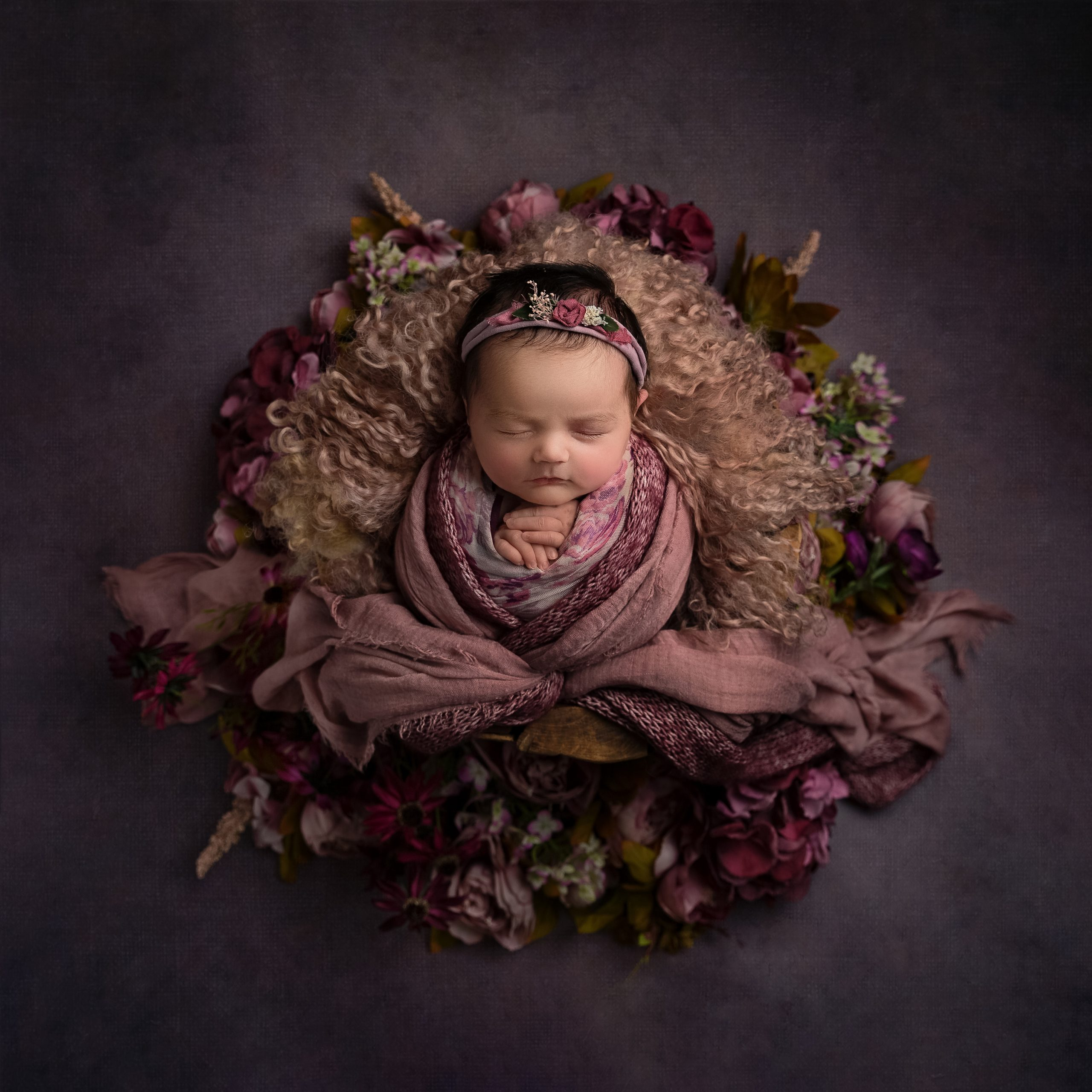 Little baby girl wrapped in a selection of pink wraps as part of my Master Craftsman in Newborn Photography panel by award winning photographer