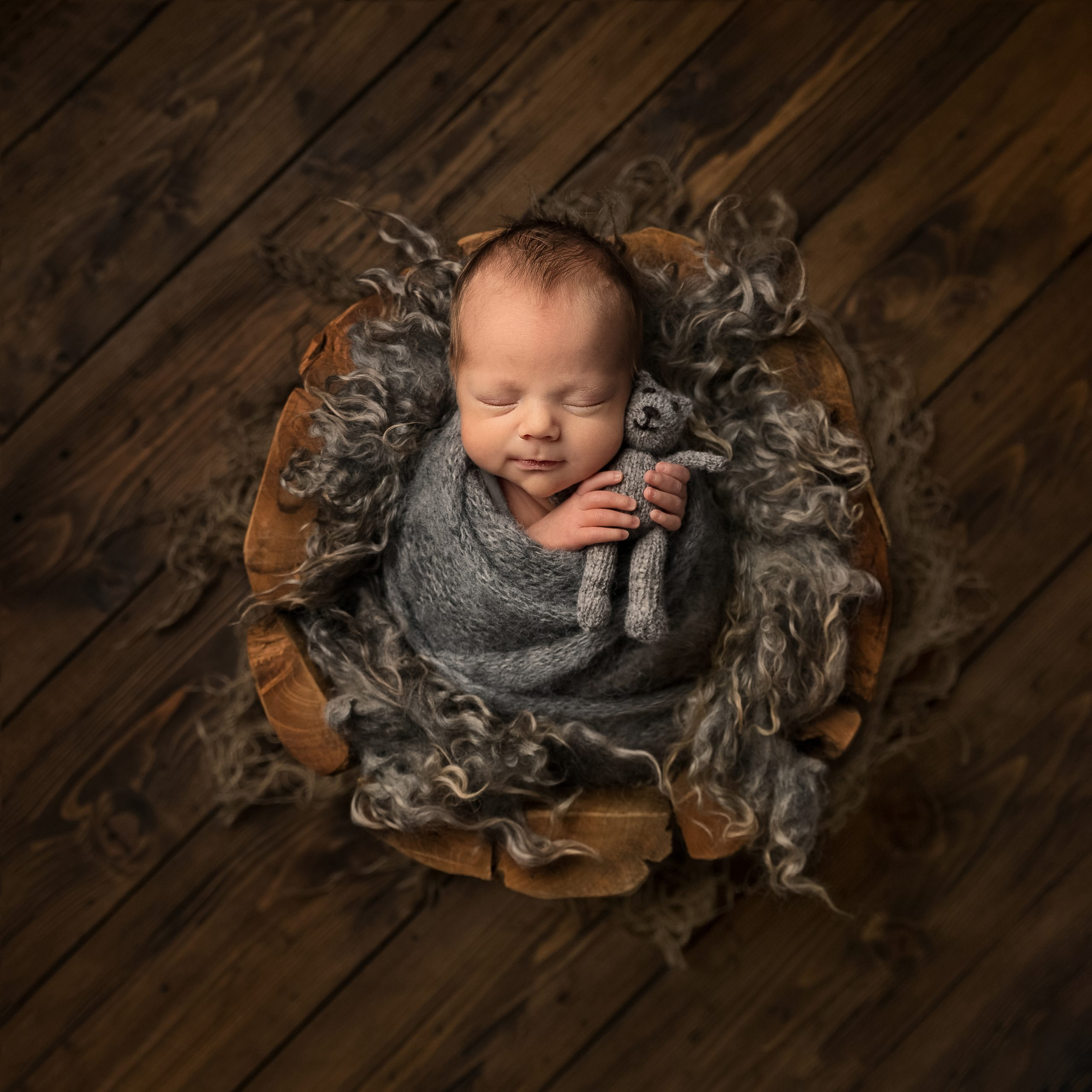 Newborn baby wrapped in grey with a little teddy as part of my Master Craftsman in Newborn Photography panel by award winning photographer