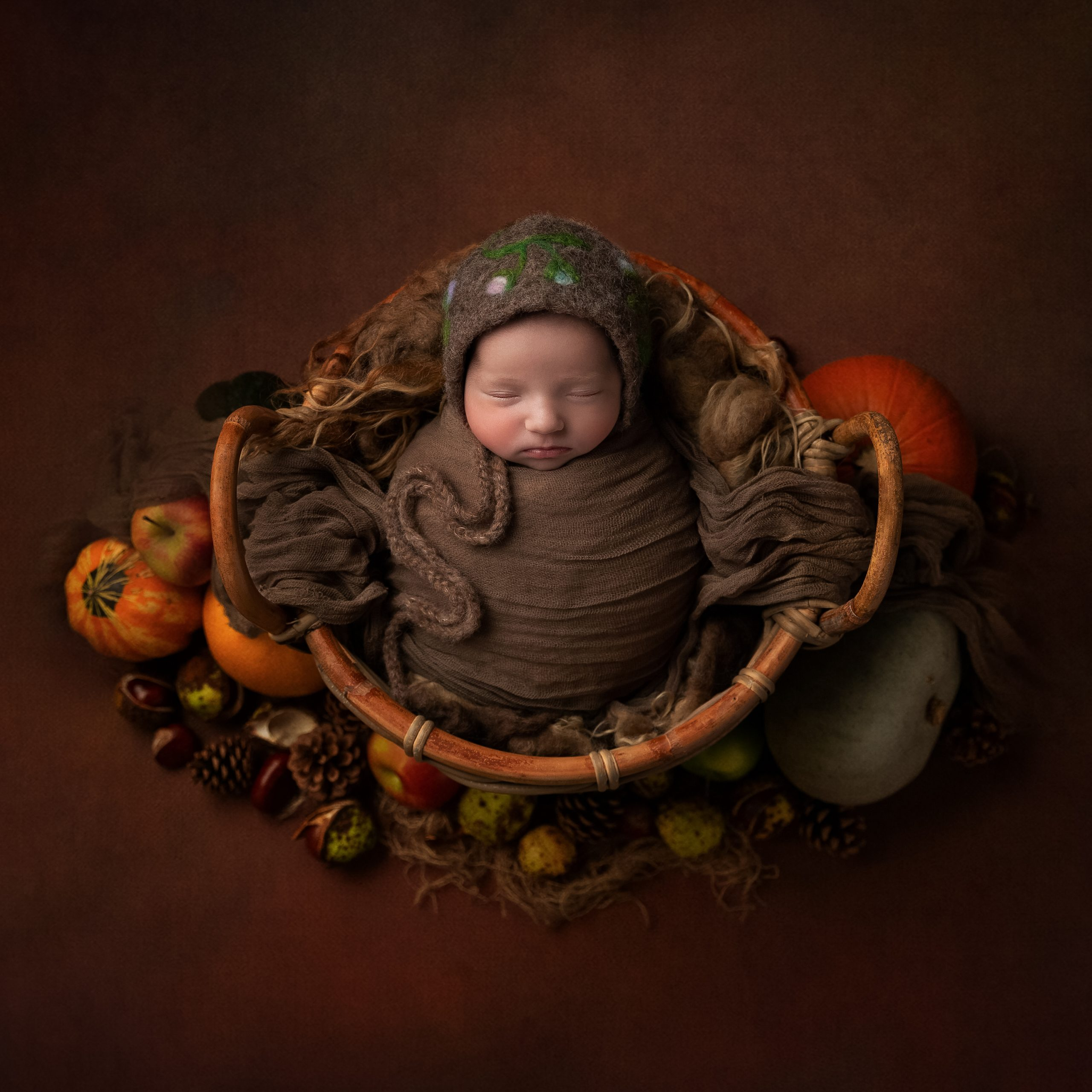 Baby girl in a floral bonnet with pumpkins as part of my Master Craftsman in Newborn Photography panel by award winning photographer