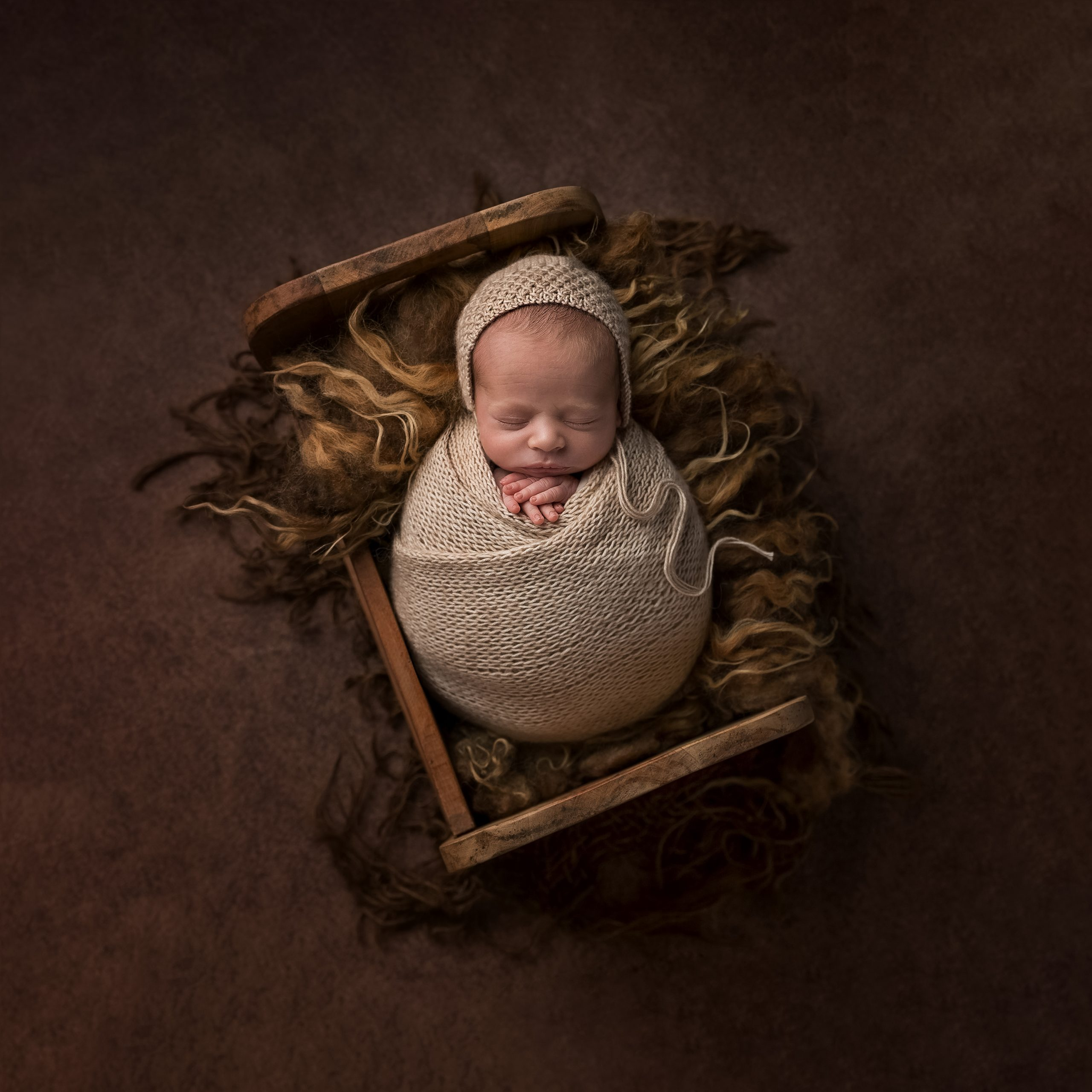 Wrapped newborn in a little cot as part of my Master Craftsman in Newborn Photography panel by award winning photographer