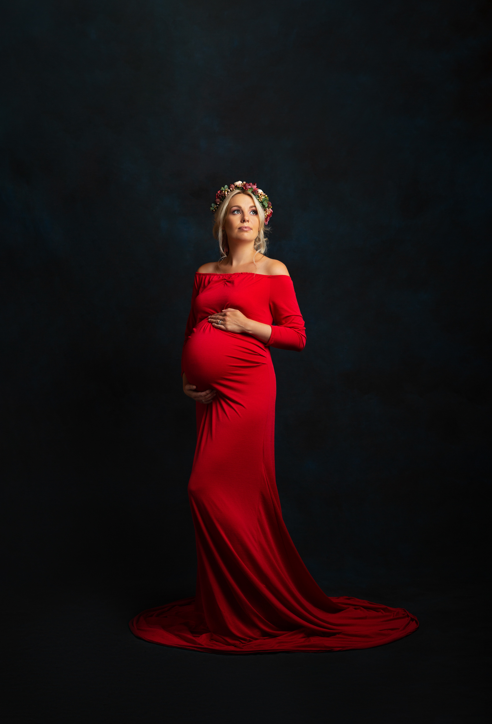 A pregnant lady in a striking red gown on a dark blue backdrop at her maternity photo shoot in Sandbach, Cheshire