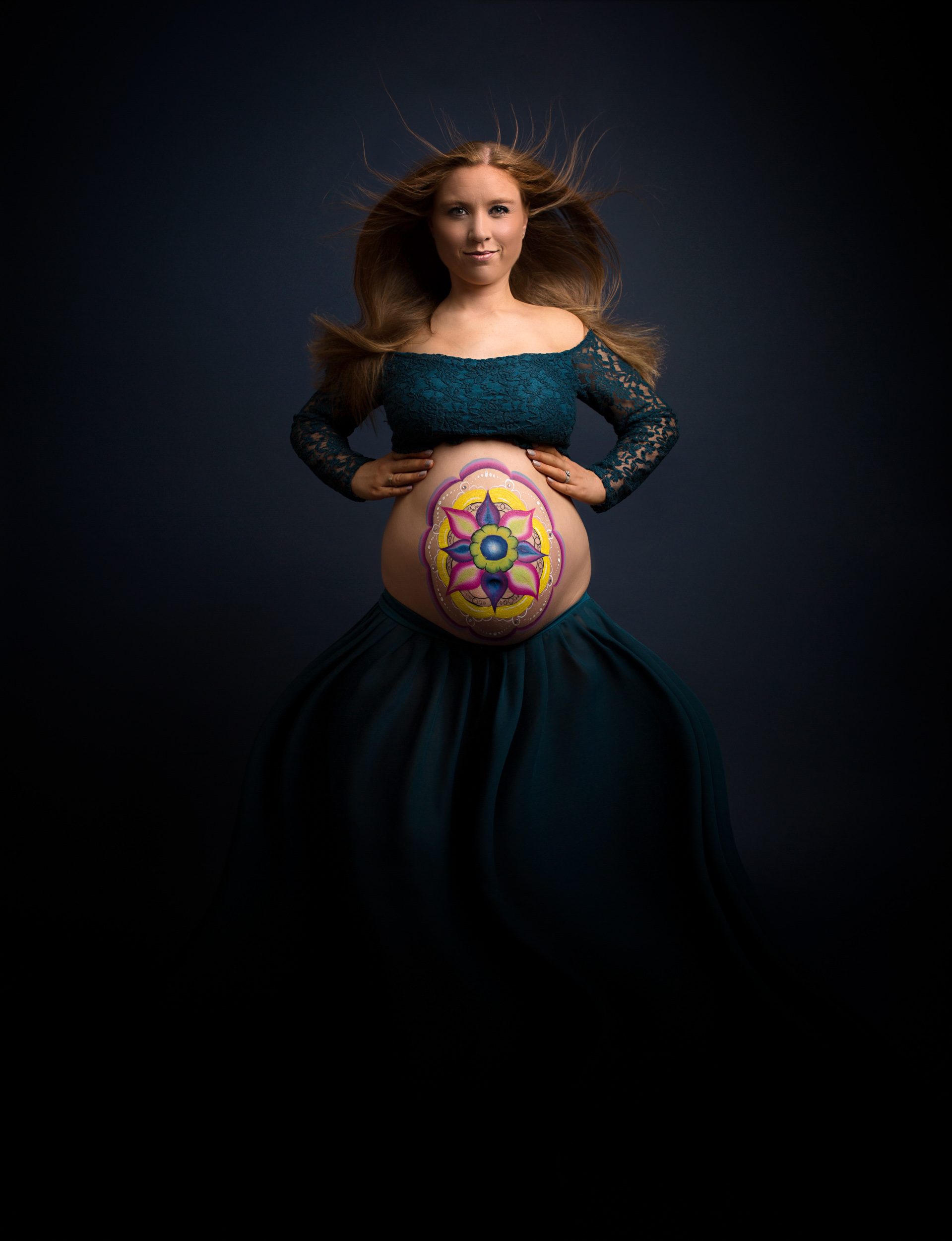 A pregnant lady with her bump painted for her photo shoot in Cheshire