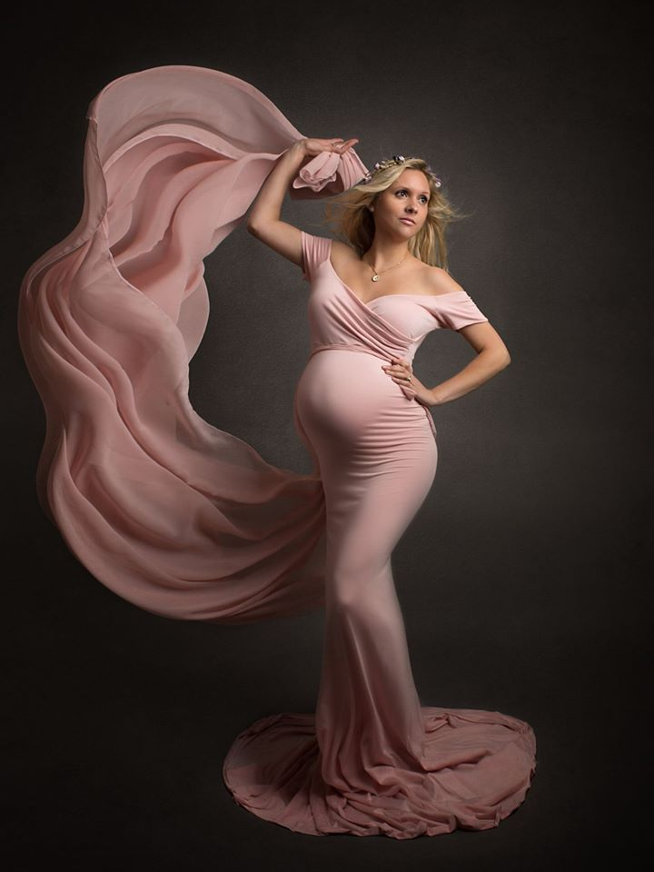 Pregnant lady posing elegantly with a swish of pink fabric flicking up into the air in Cheshire