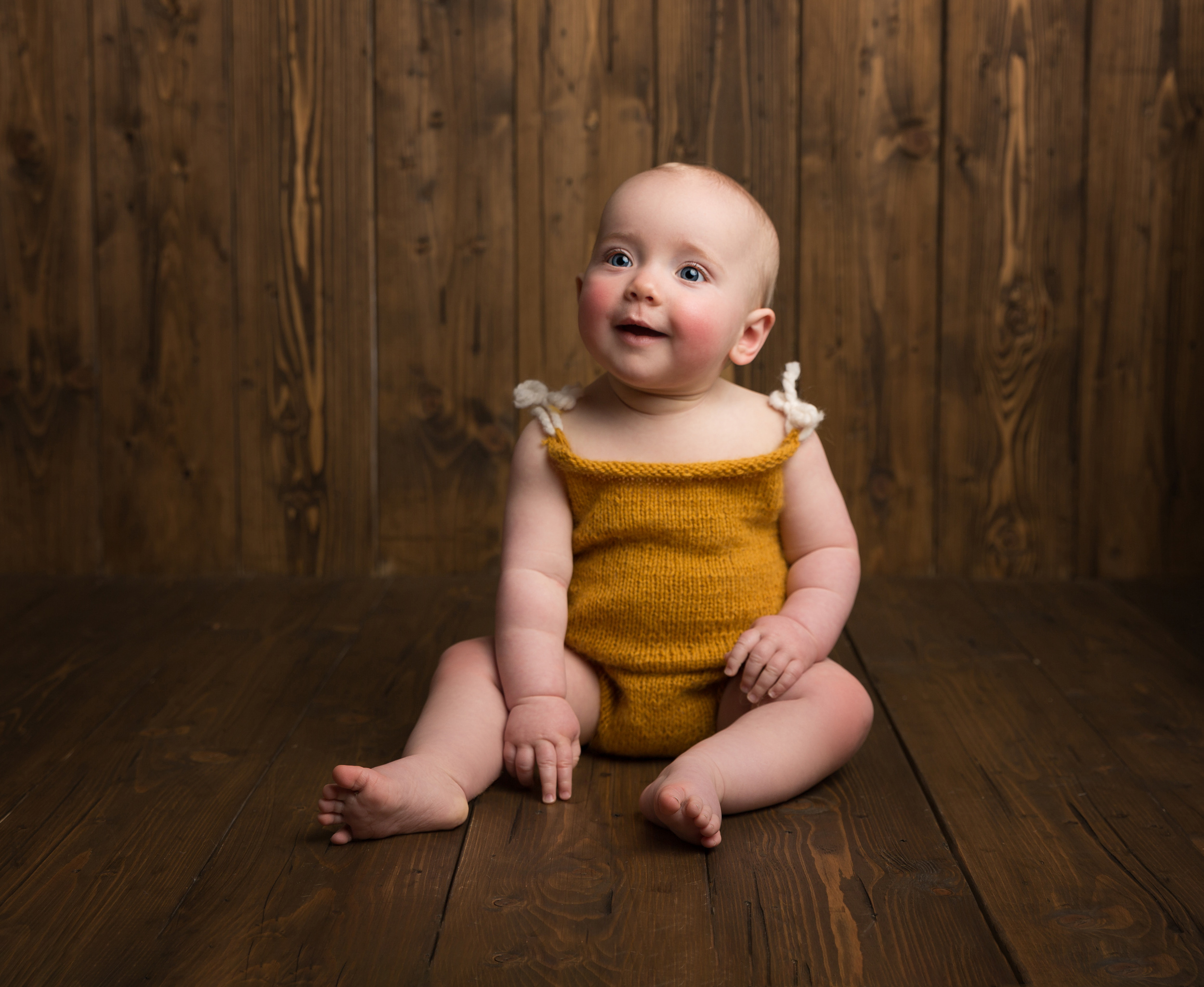 6 month old baby girl in a mustard romper on a wooden backdrop during her sitter session in Sandbach, Cheshire