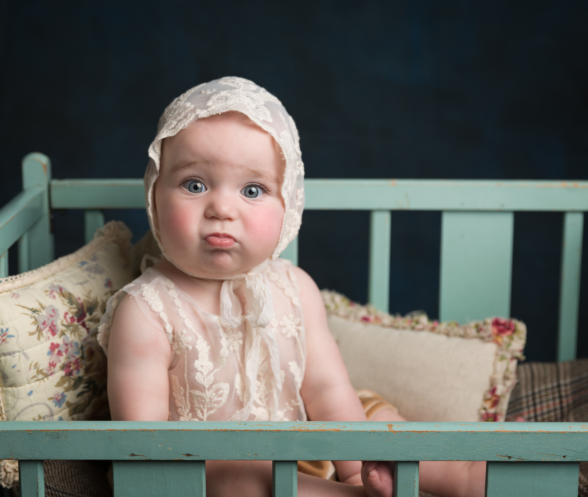 Pouting baby in a bonnet during her sitter session in Sandbach, Cheshire