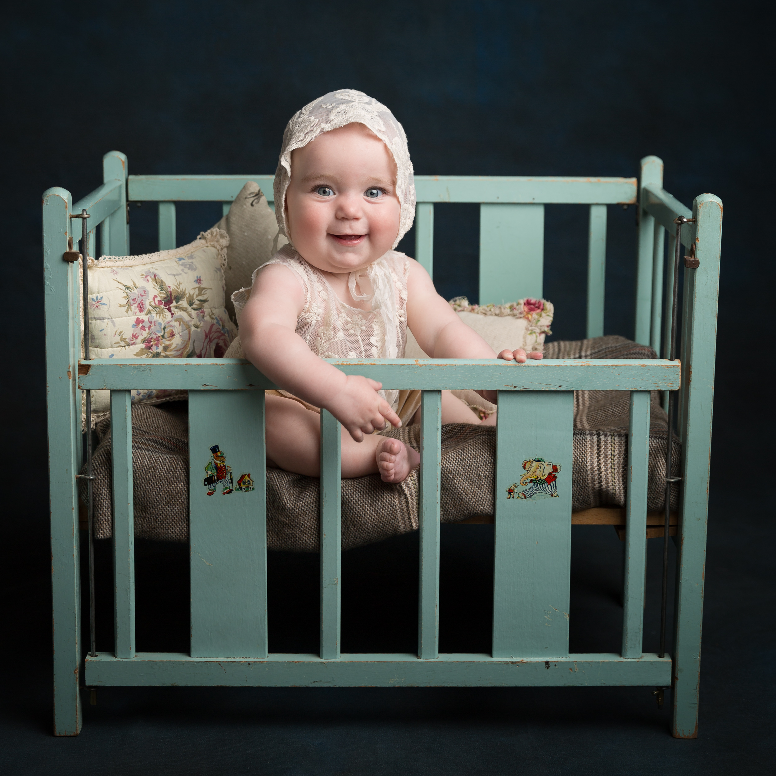 Giggling baby girl in a blue cot with bonnet on taken during a milestone portrait session in Sandbach, Cheshire