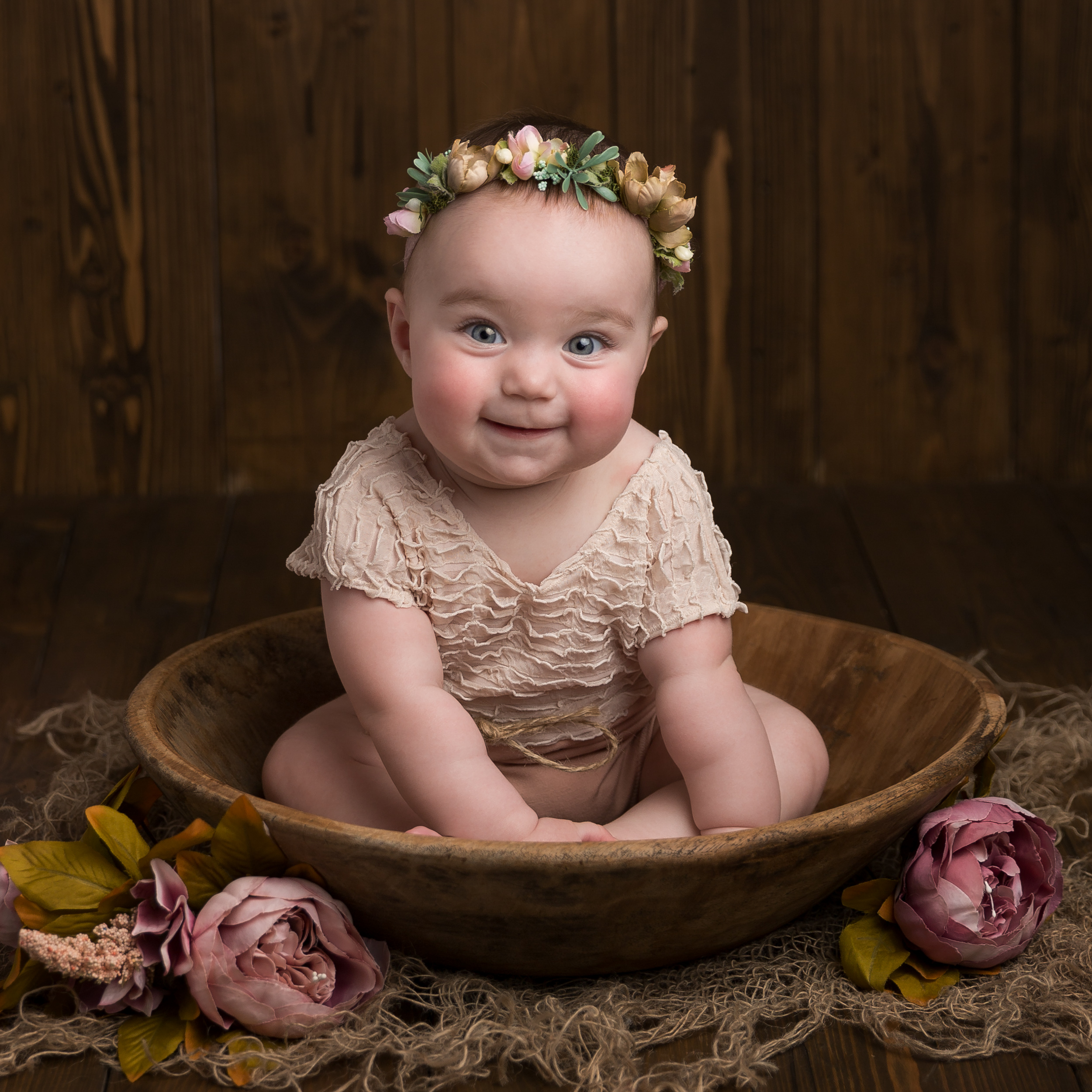 6 month old baby sitting in a bowl taken during a milestone portrait session in Sandbach, Cheshire
