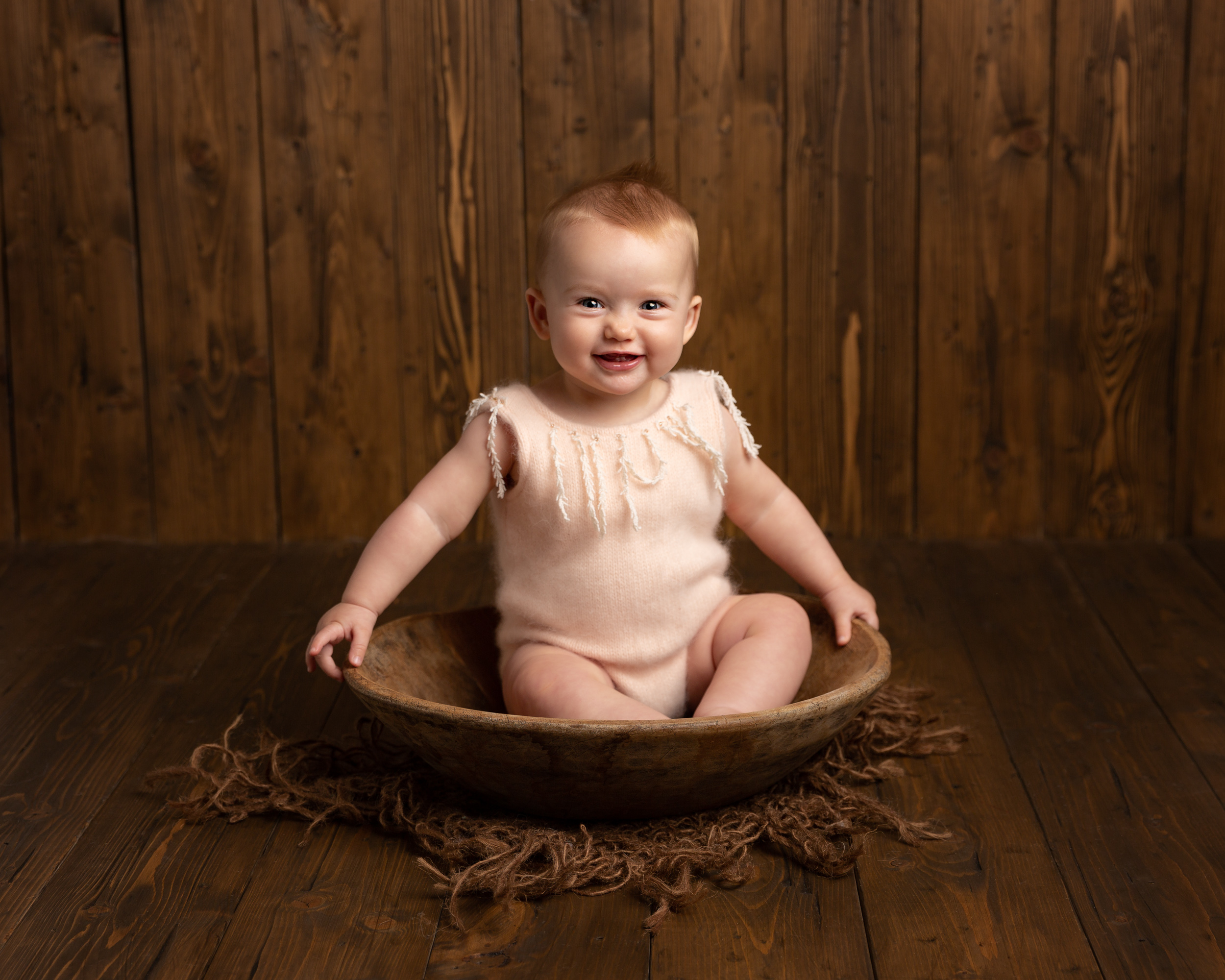 6 month old girl in a bowl on a wooden backdrop taken during a milestone portrait session in Sandbach, Cheshire