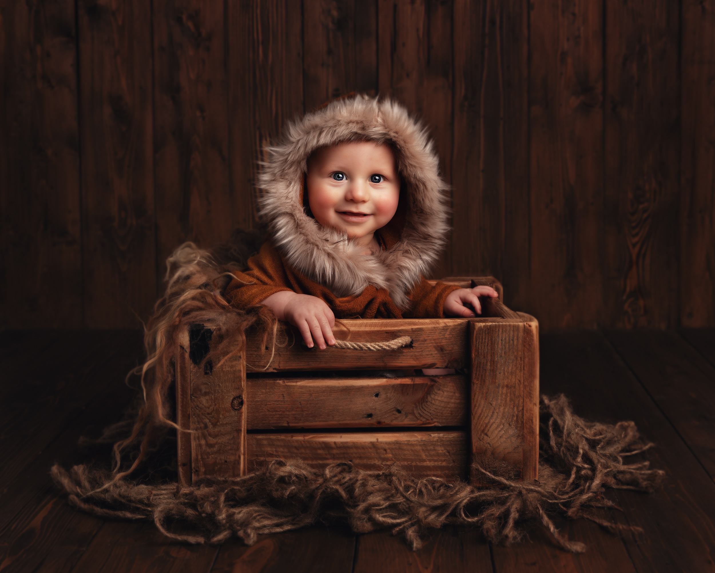 6 month old baby sitting in a crate with a fur hood during a milestone session in Sandbach, Cheshire