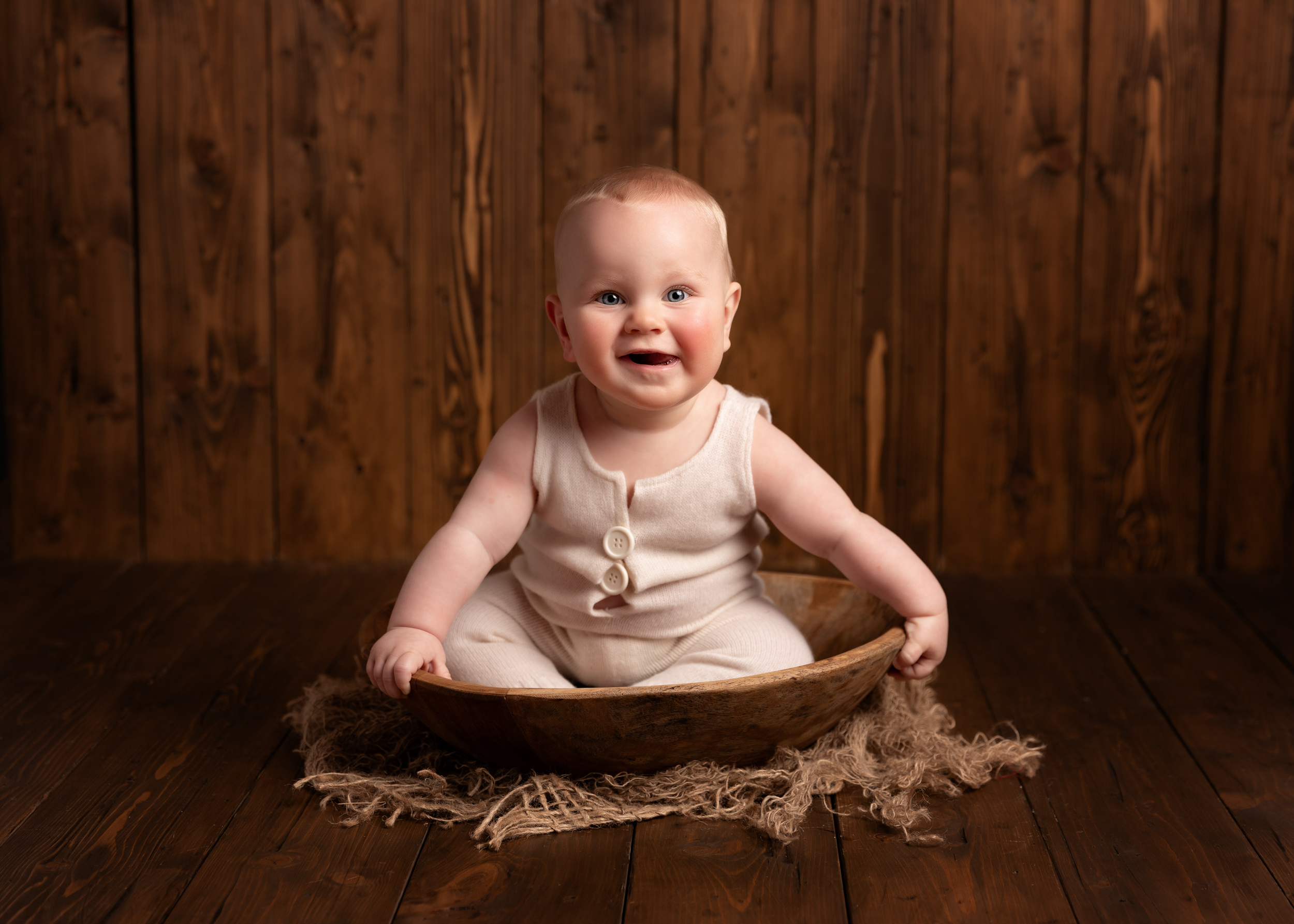 6 Month old baby sitting in a bowl with rustic wood surround in Sandbach, Cheshire