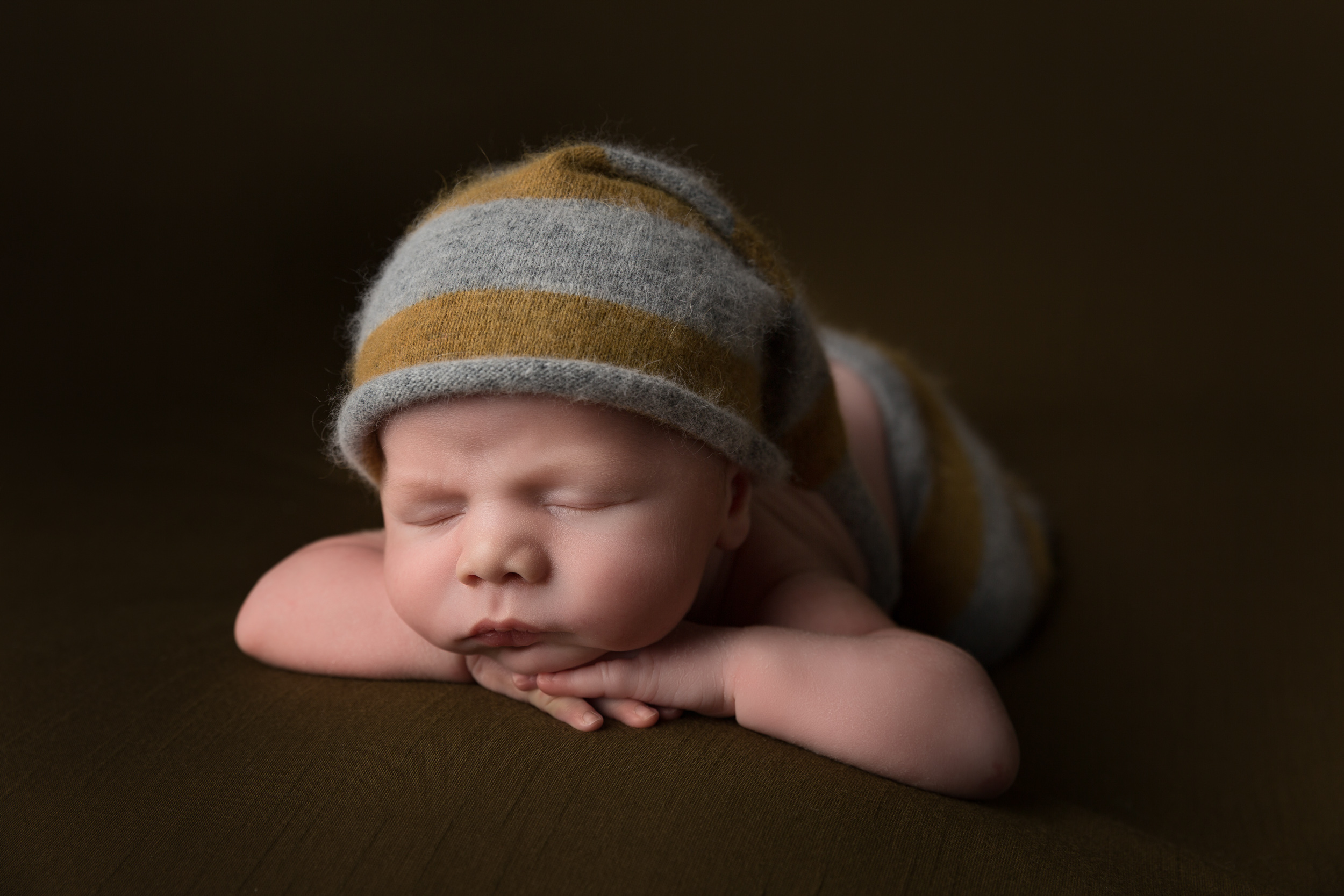 Posed newborn with a dark green colour scheme by Cheshire newborn photographer in Sandbach