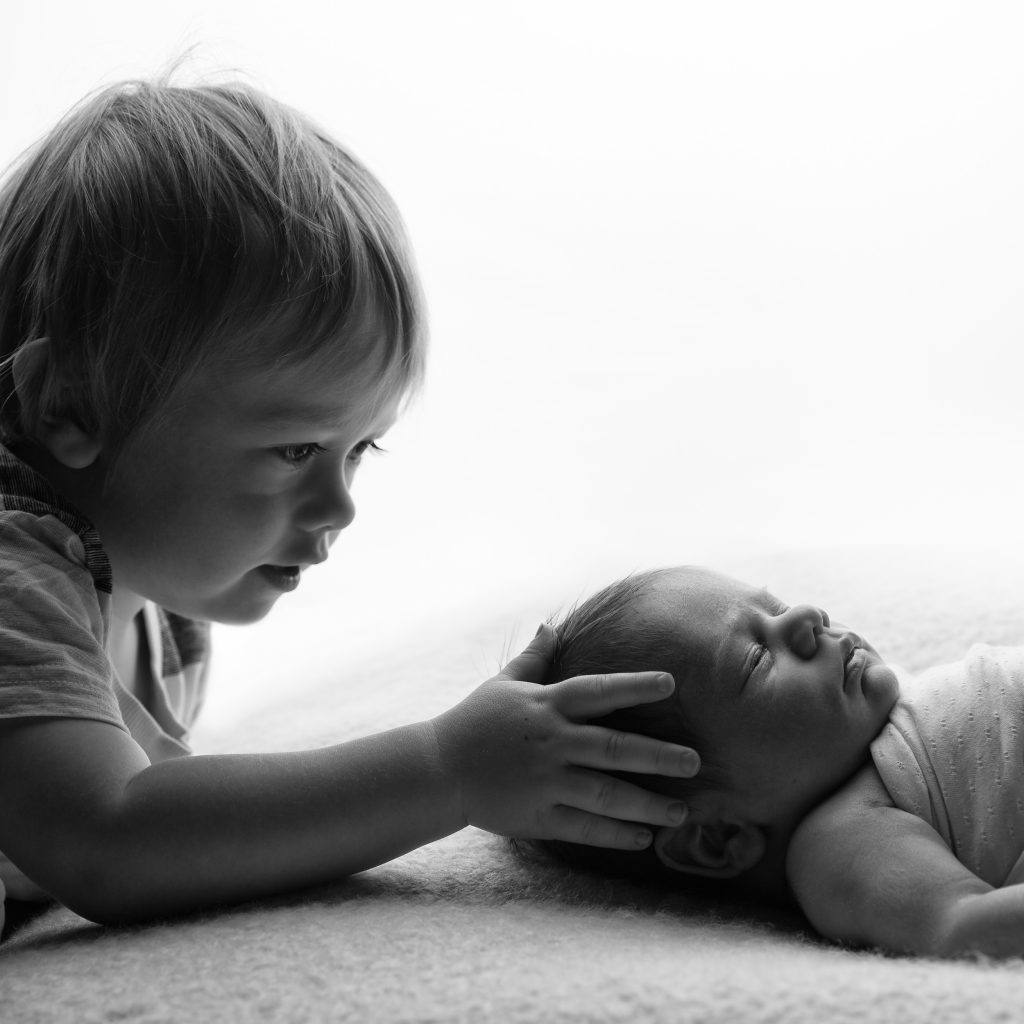 Sibling shot of newborn and his brother by Cheshire newborn photographer in Sandbach