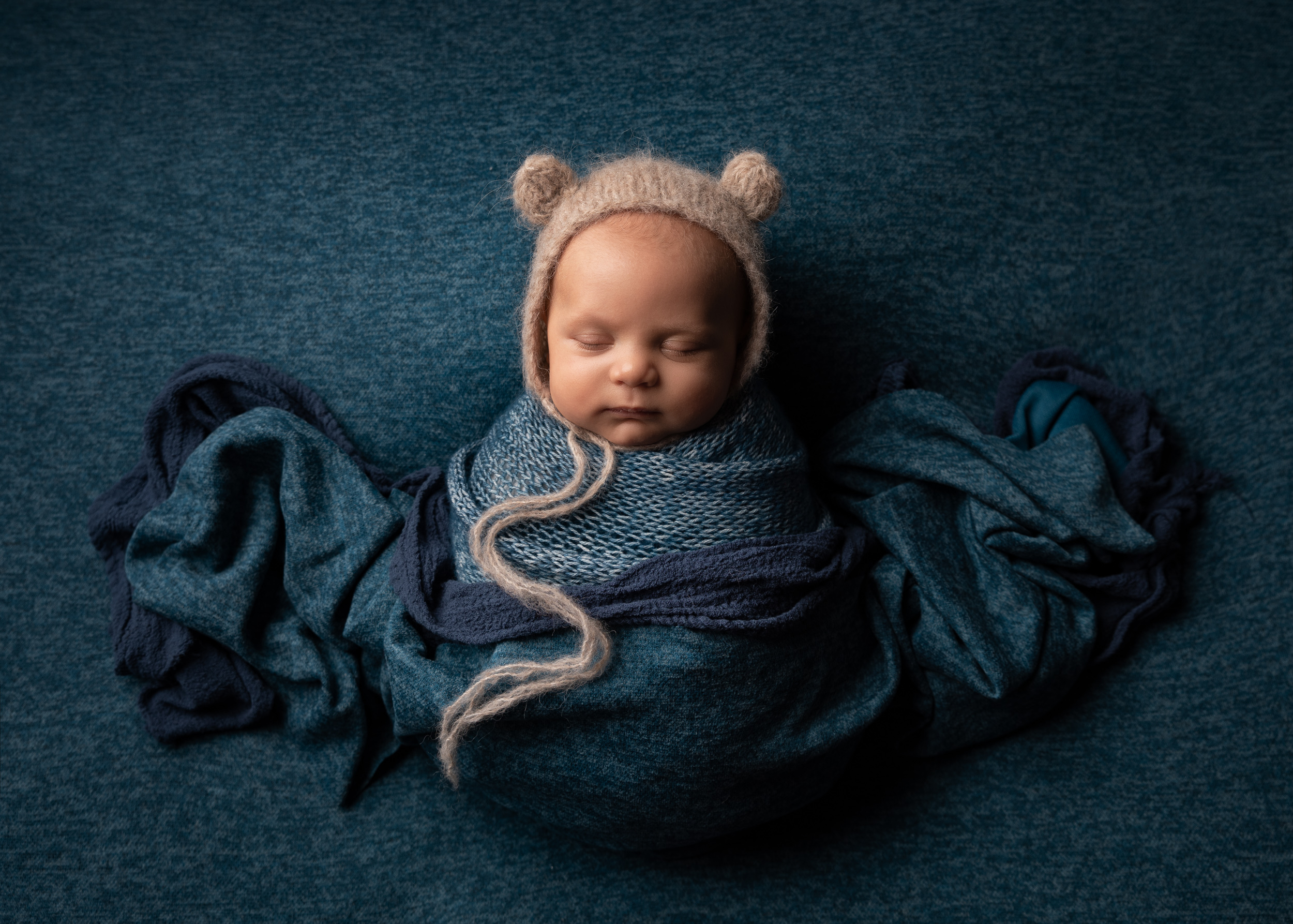 10 week old baby with blue colour scheme and bear bonnet by Cheshire newborn photographer in Sandbach