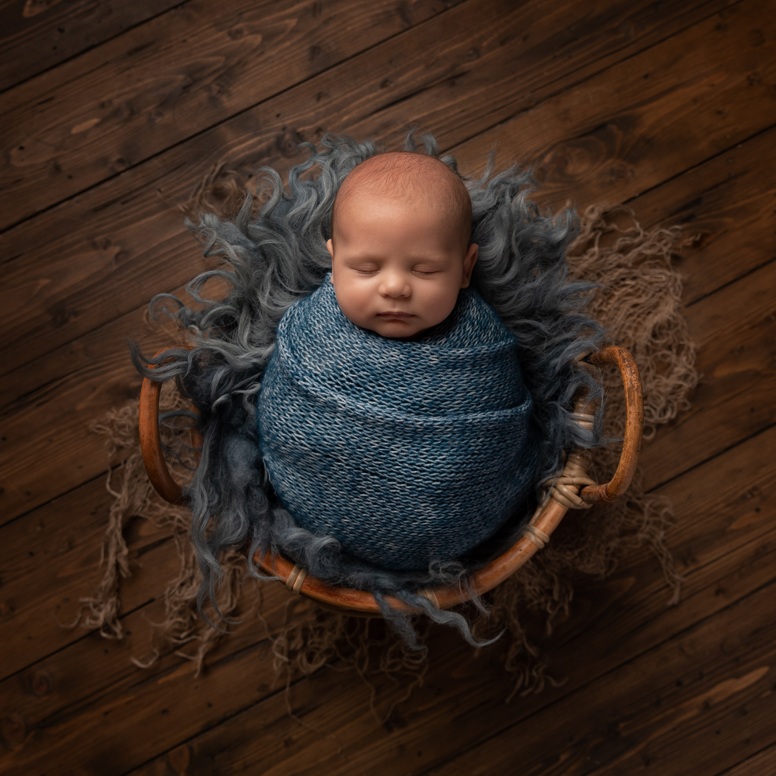 10 week old baby wrapped and asleep in a basket by Cheshire newborn photographer in Sandbach