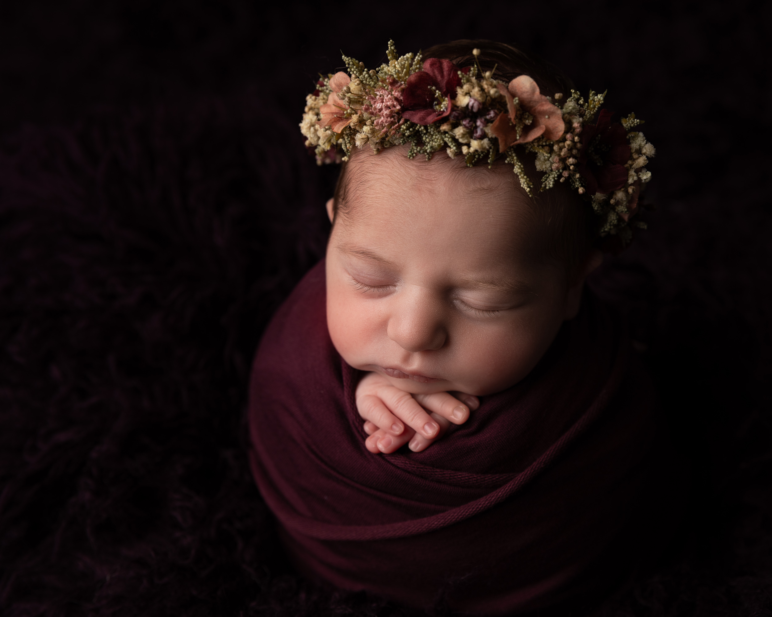 Dark toned newborn image with flower halo by Cheshire newborn photographer in Sandbach