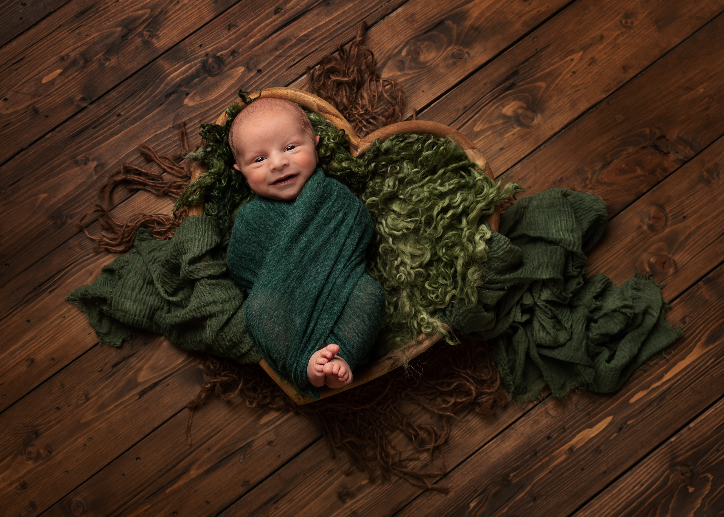 Smiling baby wrapped up in a heart prop by Cheshire newborn photographer in Sandbach