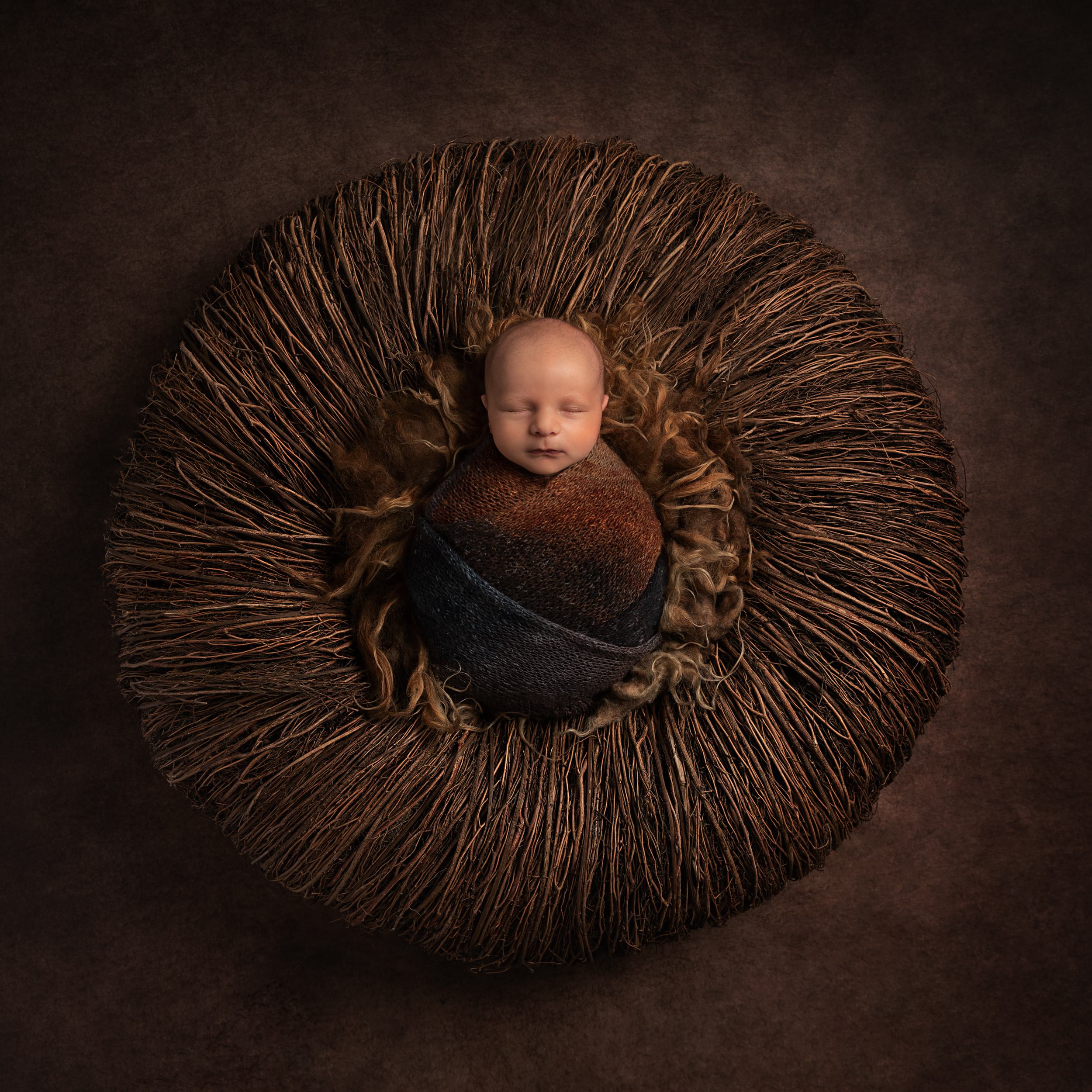 Award winning newborn photo with wrapped baby and brown colour scheme by Cheshire newborn photographer in Sandbach