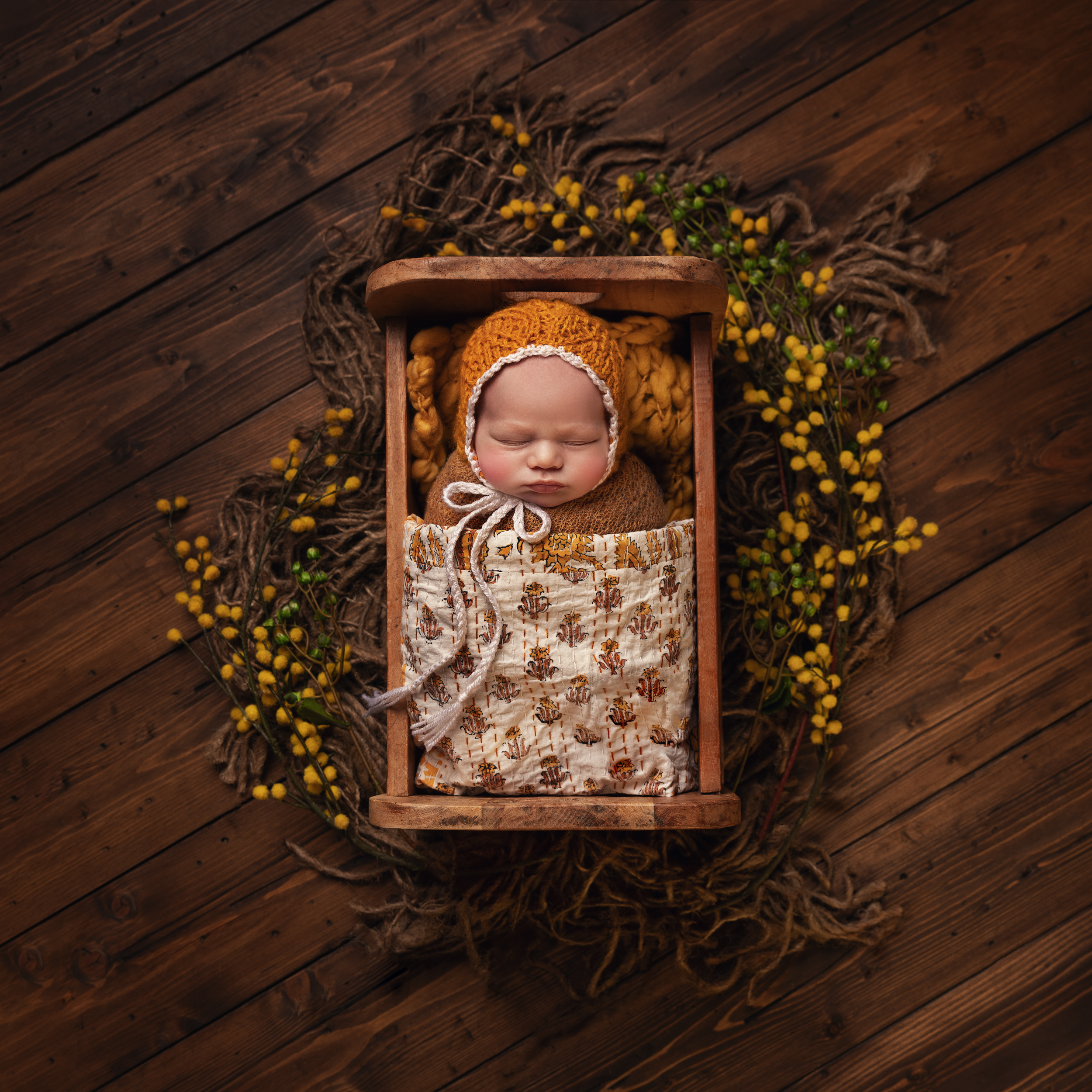 Newborn baby in a cot with white and orange colour scheme by Cheshire newborn photographer in Sandbach