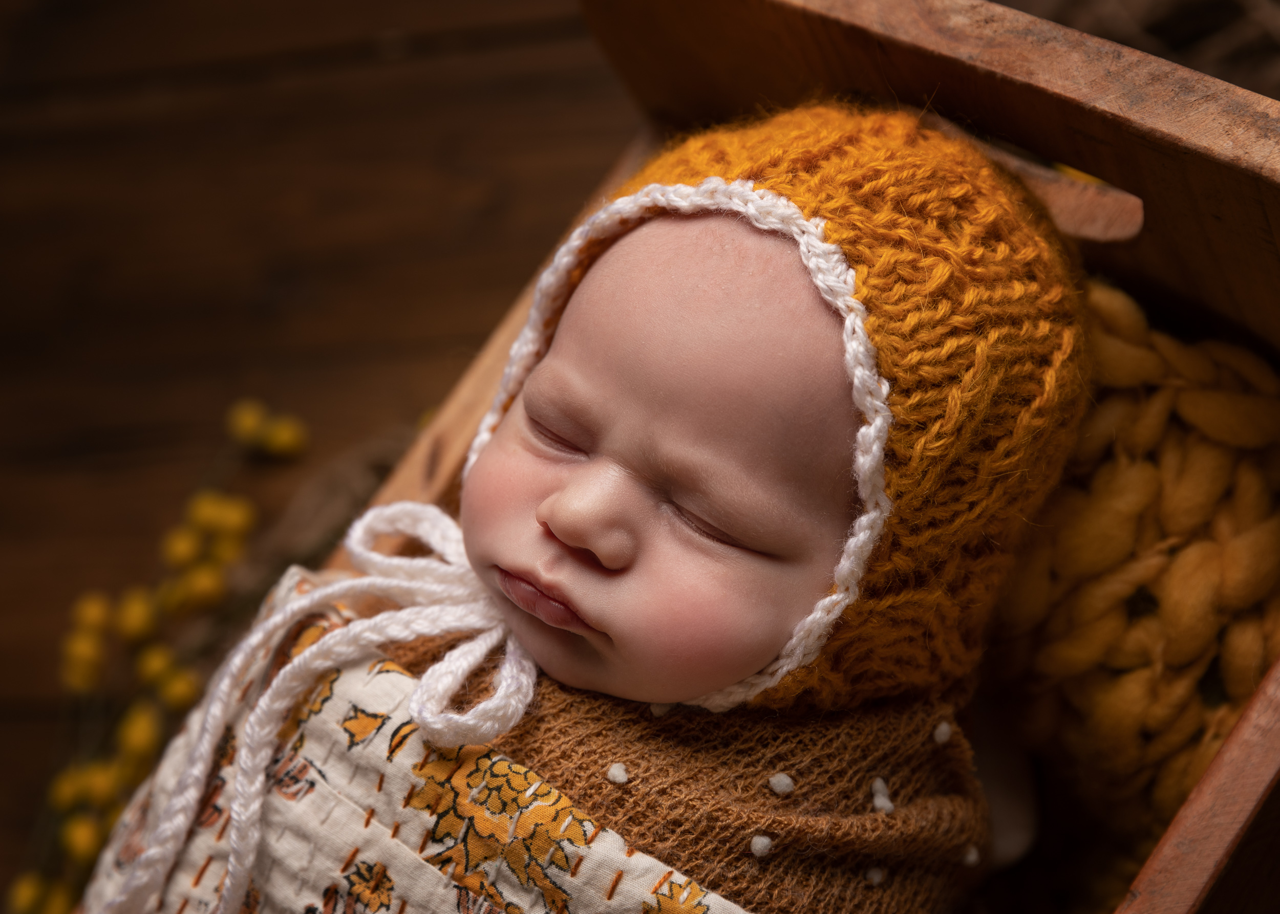 Newborn baby with mustard and white decoration by Cheshire newborn photographer in Sandbach